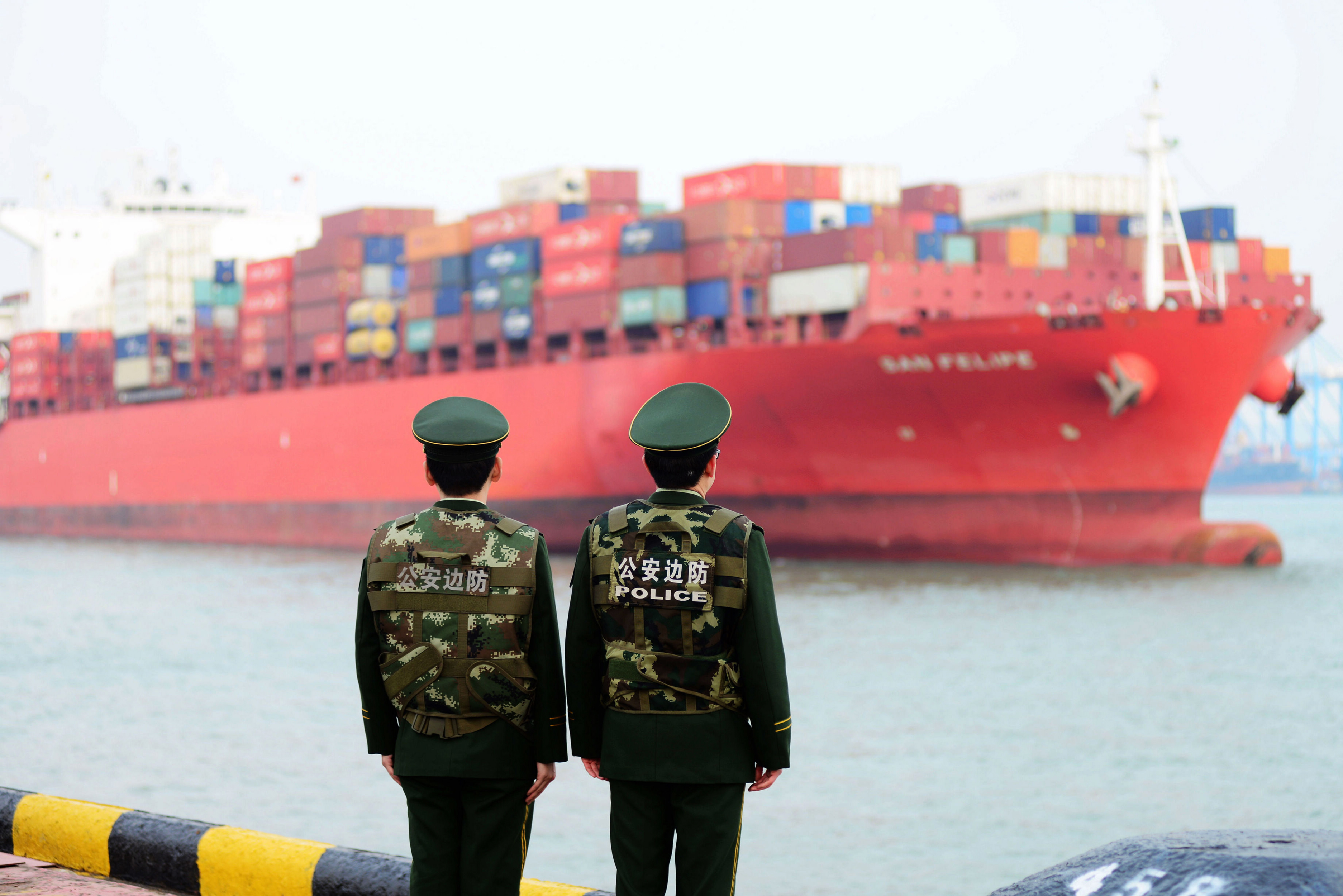 Chinese police officers watch a cargo ship at a port in Qingdao in China's eastern Shandong province on March 8, 2018. China's trade surplus with the United States narrowed for a second month in a row in February, dropping to 21 billion USD, official data showed on March 8, amid rising trade tensions with the Trump administration. / AFP PHOTO / - / China OUT (Photo credit should read -/AFP/Getty Images)