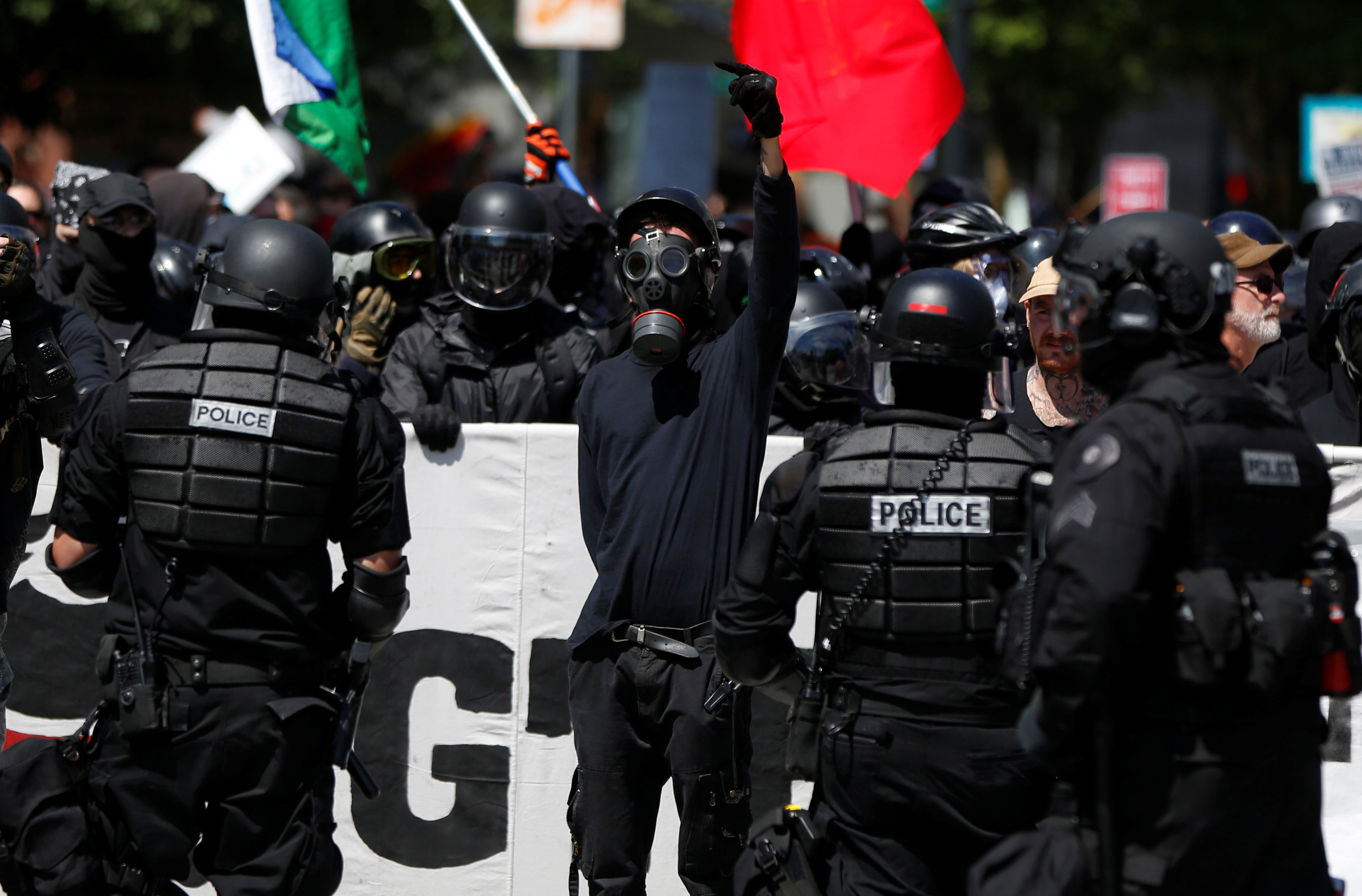 Counter-demonstrators are held back by police during a rally in Portland