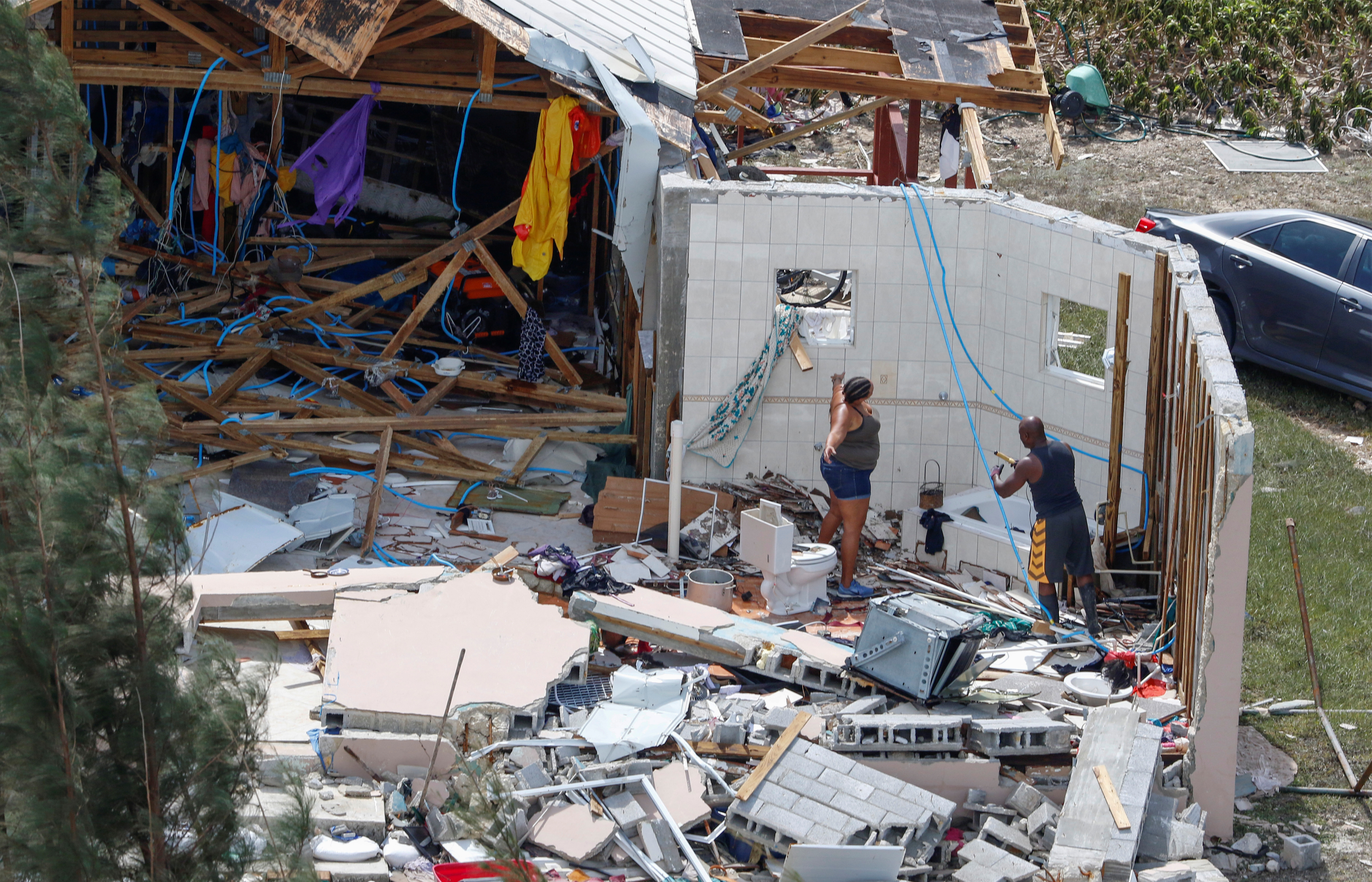 Residents look through debris after hurricane Dorian hit the Grand Bahama Island in the Bahamas, September 4, 2019. (REUTERS/Joe Skipper)