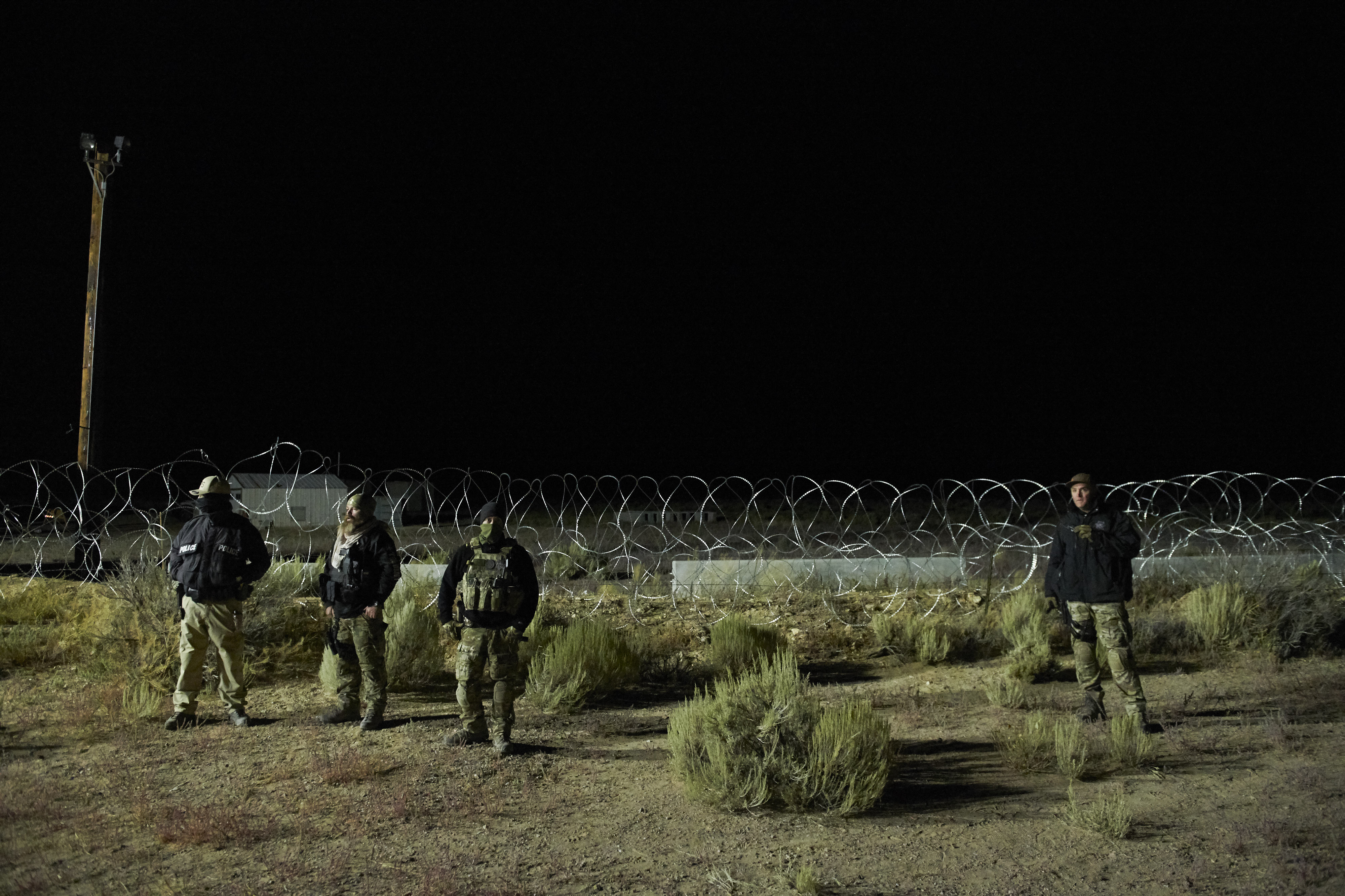 "Members of law enforcement stand near barb wire, as people gathered to ""storm"" Area 51, at an entrance to the military facility near Rachel, Nevada on September 20, 2019. (Photo by BRIDGET BENNETT/AFP/Getty Images)"