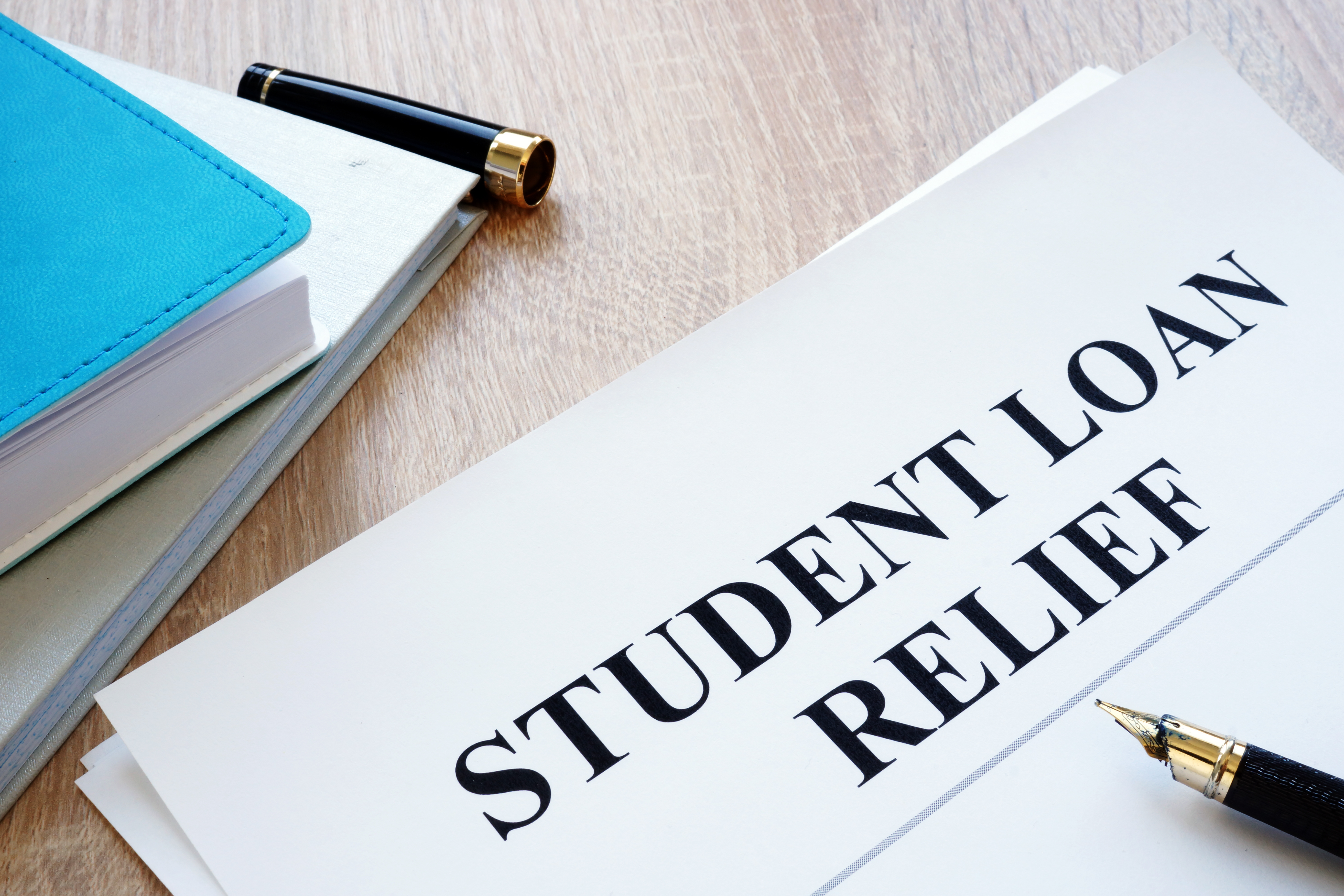 Student loan relief papers on the desk. - Image