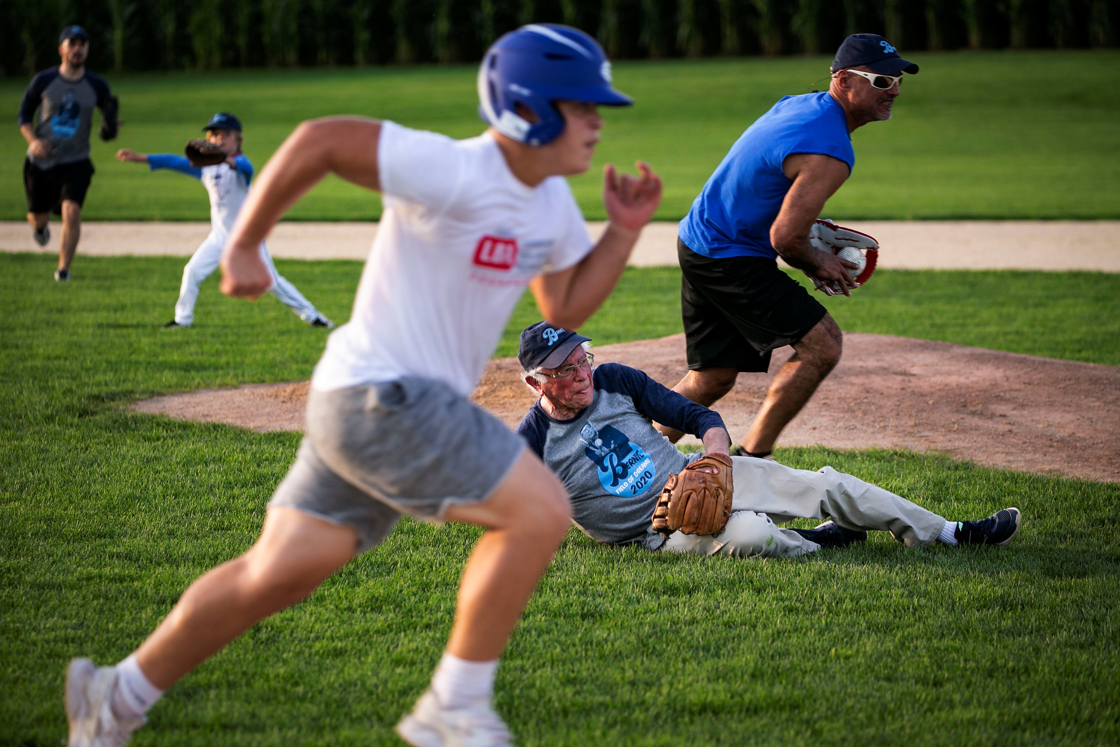 """2020 Democratic U.S. presidential candidate and U.S. Senator Bernie Sanders dives for the ball during a baseball game between his staff, """"The Revolutionaries,"""" and the Leaders Believers Achievers Foundation at the """"Field of Dreams"""" movie site in Dyersville, Iowa, U.S., August 19, 2019. REUTERS/Al Drago"""