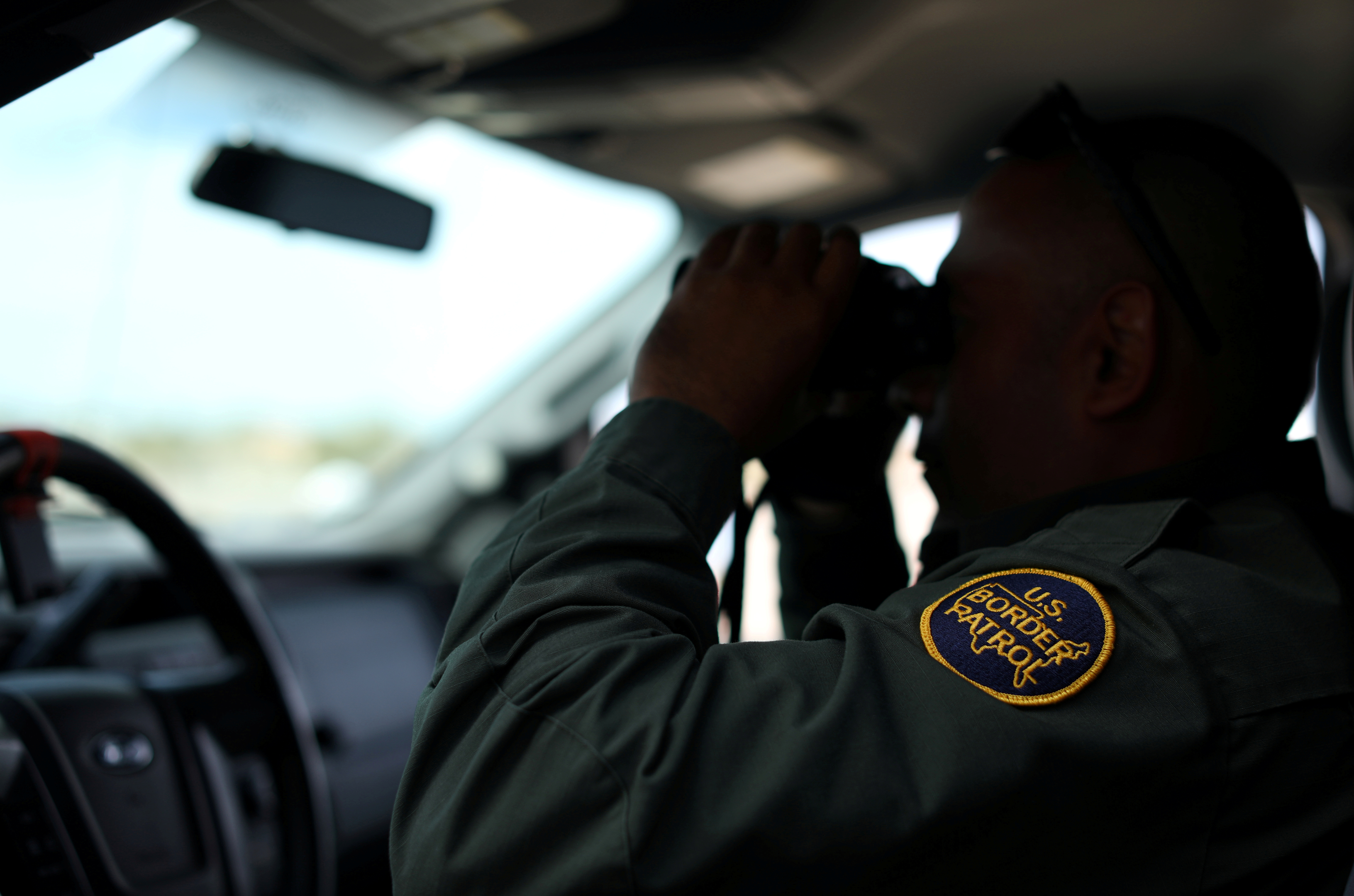 FILE PHOTO: A U.S. border patrol agent keeps watch along the fence next to the Mexican border in Calexico, California