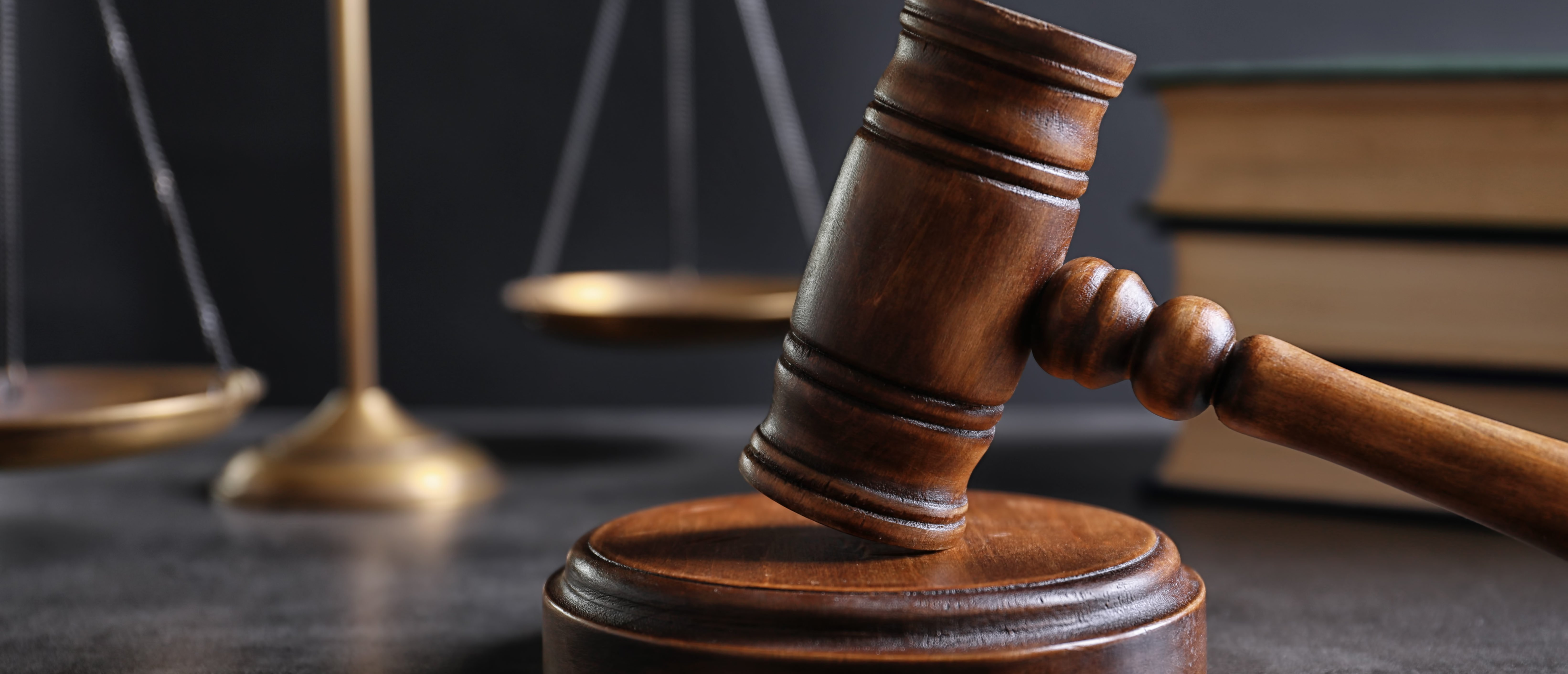 Judge's gavel and blurred scales on background. (New Africa/Shutterstock)