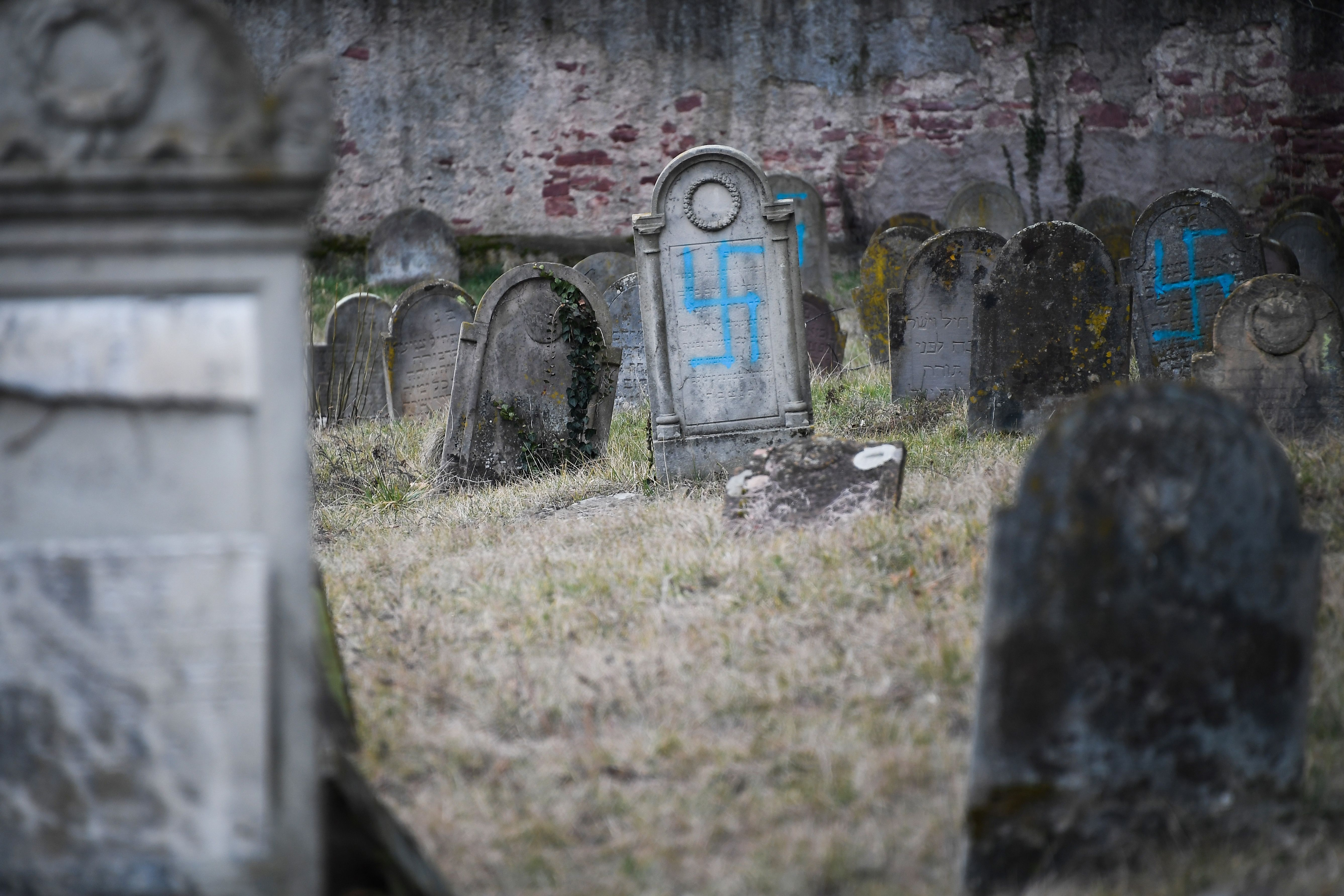 A picture taken on February 19, 2019 shows graves vandalised with swastikas at the Jewish cemetery in Quatzenheim, on the day of a nationwide marches against a rise in anti-Semitic attacks. - Around 80 graves have been vandalised at the Jewish cemetery in the village of Quatzenheim, close to the border with Germany in the Alsace region, which were discovered early February 19, 2019, according to a statement from the regional security office. (Photo by Frederick FLORIN / AFP) (Photo credit should read FREDERICK FLORIN/AFP/Getty Images)