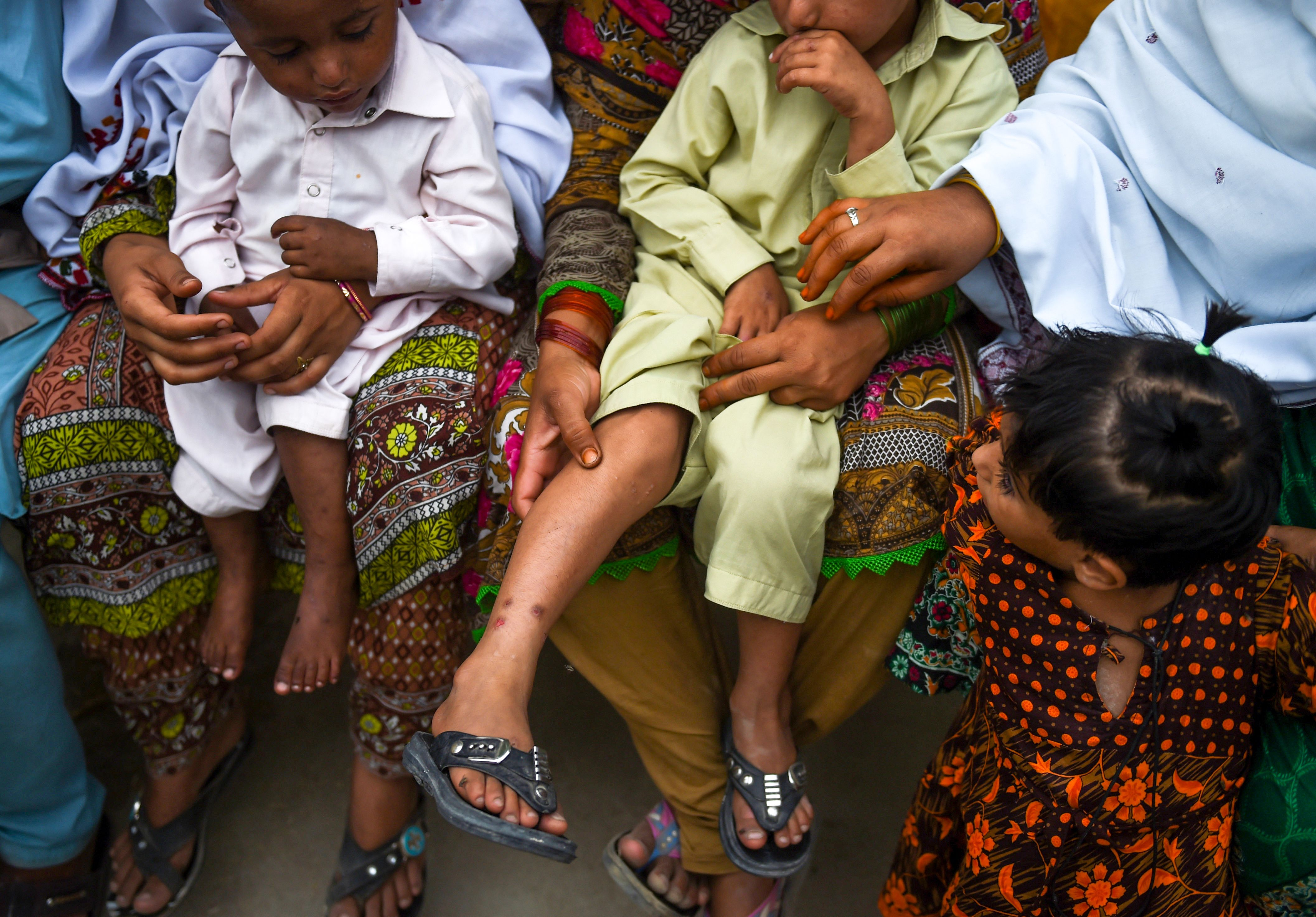 In this image taken on May 8, 2019, Pakistani women hold their HIV infected children as they gather at a house at Wasayo village in Rato Dero in the district of Larkana of the southern Sindh province. (Photo credit should read RIZWAN TABASSUM/AFP/Getty Images)