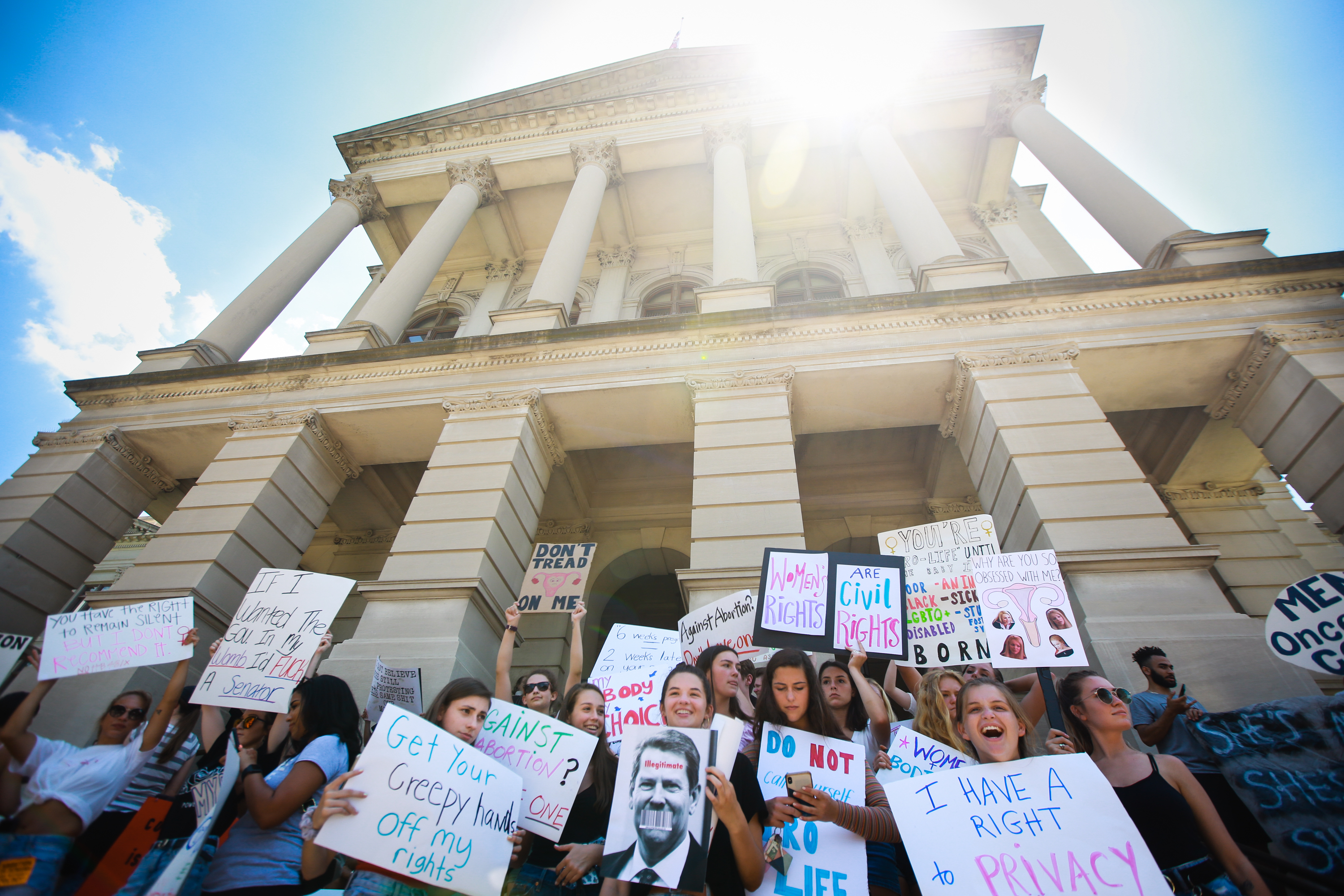 """ATLANTA, GA - MAY 21: Young women from Paideia High School hold signs during a protest against recently passed abortion ban bills at the Georgia State Capitol building, on May 21, 2019 in Atlanta, Georgia. The Georgia """"heartbeat"""" bill would ban abortion when a fetal heartbeat is detected. The Alabama abortion law, signed by Gov. Kay Ivey last week, includes no exceptions for cases of rape and incest, outlawing all abortions except when necessary to prevent serious health problems for the woman. Though women are exempt from criminal and civil liability, the new law punishes doctors for performing an abortion, making the procedure a Class A felony punishable by up to 99 years in prison (Photo by Elijah Nouvelage/Getty Images)"""