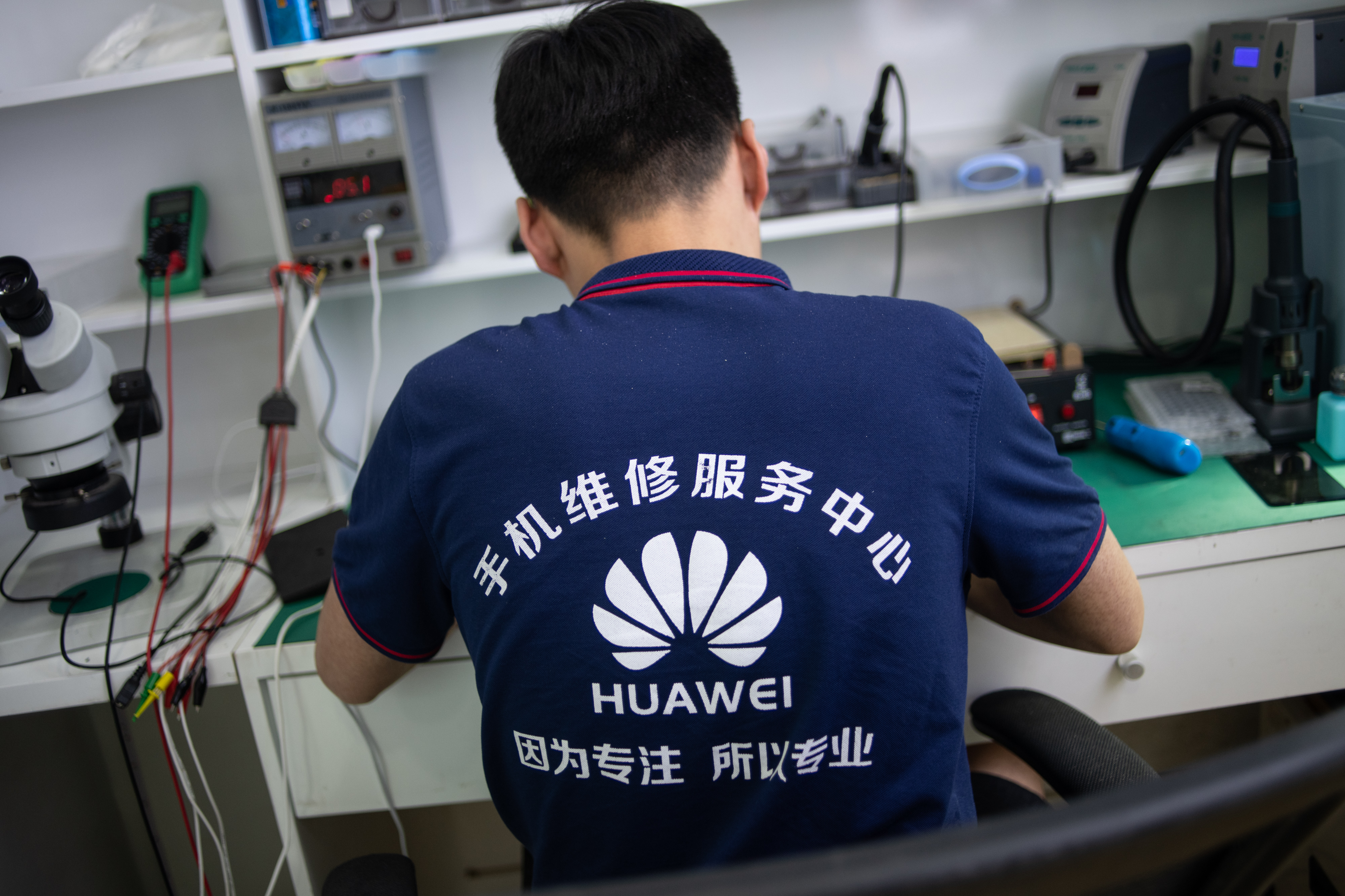 In this photo taken on May 27, 2019, a worker wearing a Huawei shirt fixes phones at a retail store in Beijing. - China is digging in for a tough period of deteriorating ties with the United States, fanning the flames of patriotism with Korean War films, a viral song on the trade war, and editorials lambasting Washington. (Photo by FRED DUFOUR / AFP) (Photo credit should read FRED DUFOUR/AFP/Getty Images)
