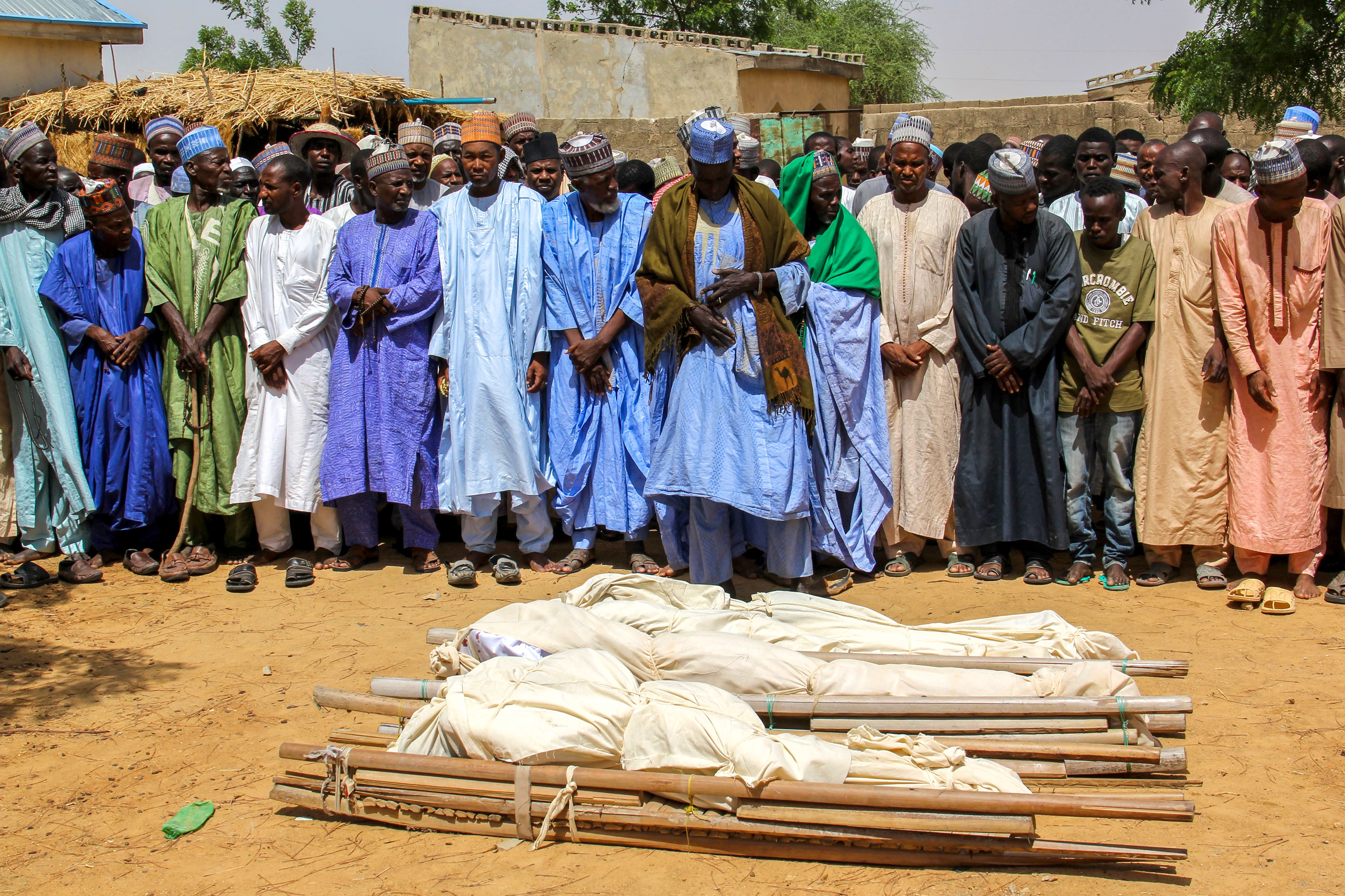 TOPSHOT - Men pray next to coffins during a burial ceremony, after two people were killed by Boko Haram fighters in Dalori camp for internally displaced people, near Maiduguri, on July 26, 2019. - Two people were killed and several wounded when Boko Haram fighters raided a camp for people displaced by the jihadist conflict in northeast Nigeria, emergency services said on July 26, 2019. Dozens of Islamist militants on motorcycles and two motorised rickshaws stormed into Dalori camp on Thursday, shooting people and looting food supplies after overrunning a nearby military base. (Photo by Audu MARTE / AFP) (Photo credit should read AUDU MARTE/AFP/Getty Images)