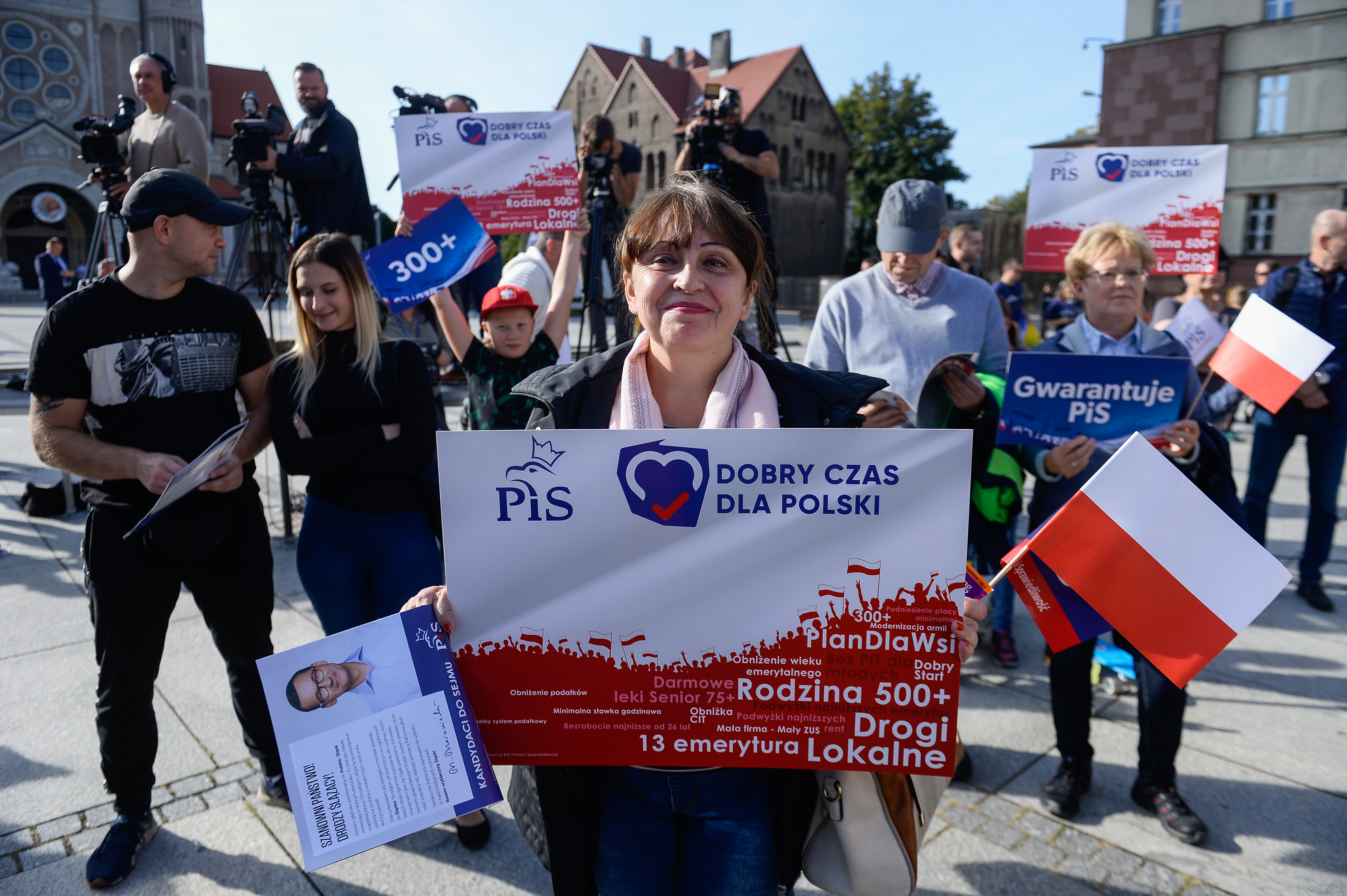 "RUDA SLANSKA, POLAND - SEPTEMBER 21: A woman holds a Law and Justice banner as the Polish Prime Minister, Mateusz Morawiecki delivers a speech during a campaign event on September, 21 in Ruda Slanska, Poland. The ruling Law and Justice Party, a conservative right-wing party with close ties to the Polish Church, within Poland's general election less than a month away, as been campaigning against LGBT equal rights and has announced several proposal packages promising changes on social spending, journalism laws, the prosecution of parliamentarians, ""500+"" child program to cover all children, a bonus payment for retirees exempting workers among others. (Photo by Omar Marques/Getty Images)"