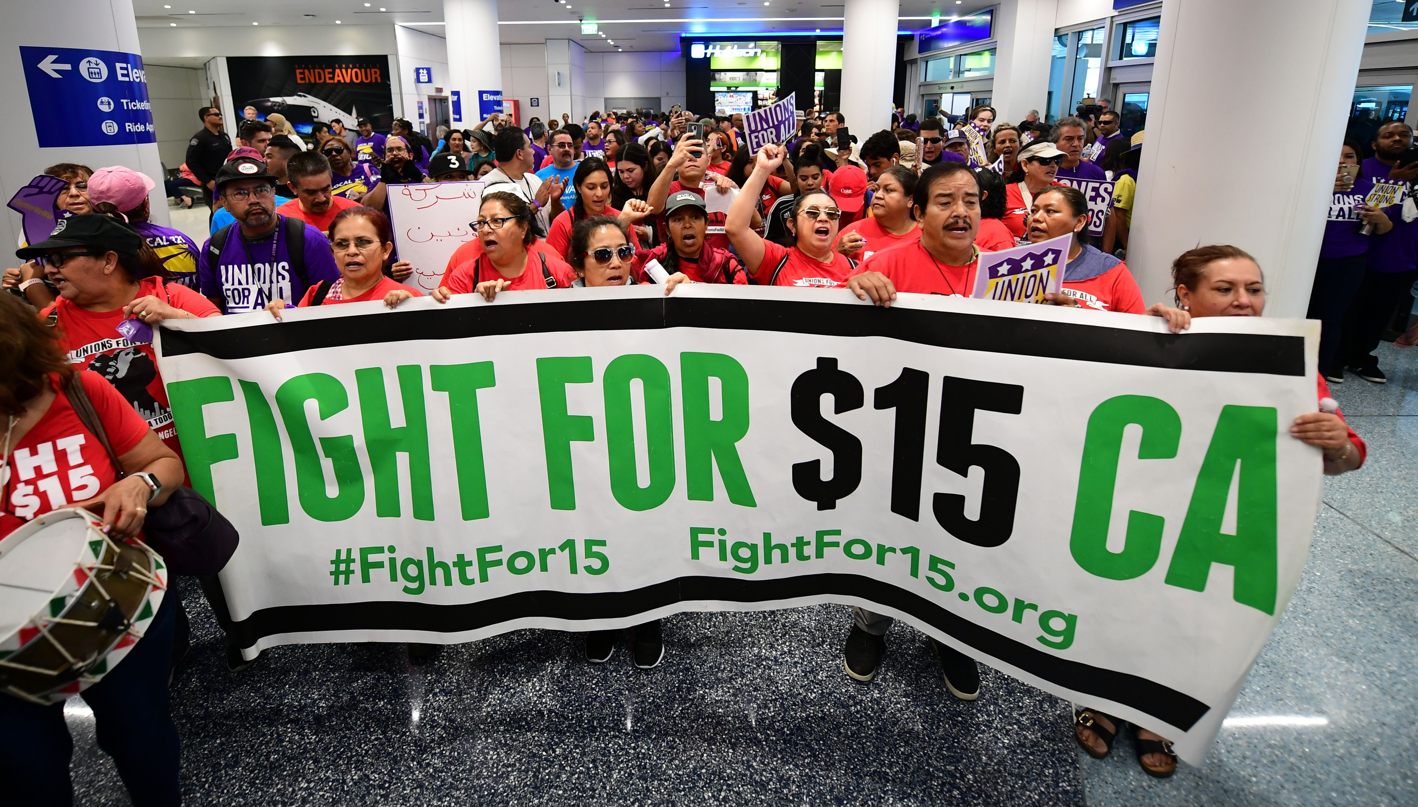 "A banner for a $15 dollar per hour minimum wage is displayed as airport employees are joined by drivers from Uber and Lyft and other southern California workers for a protest at Los Angeles International Airport in Los Angeles, California on October 2, 2019, demanding elected officials pledge their support for the ""Unions for All"" movement. (Photo by Frederic J. BROWN / AFP) (Photo by FREDERIC J. BROWN/AFP via Getty Images)"