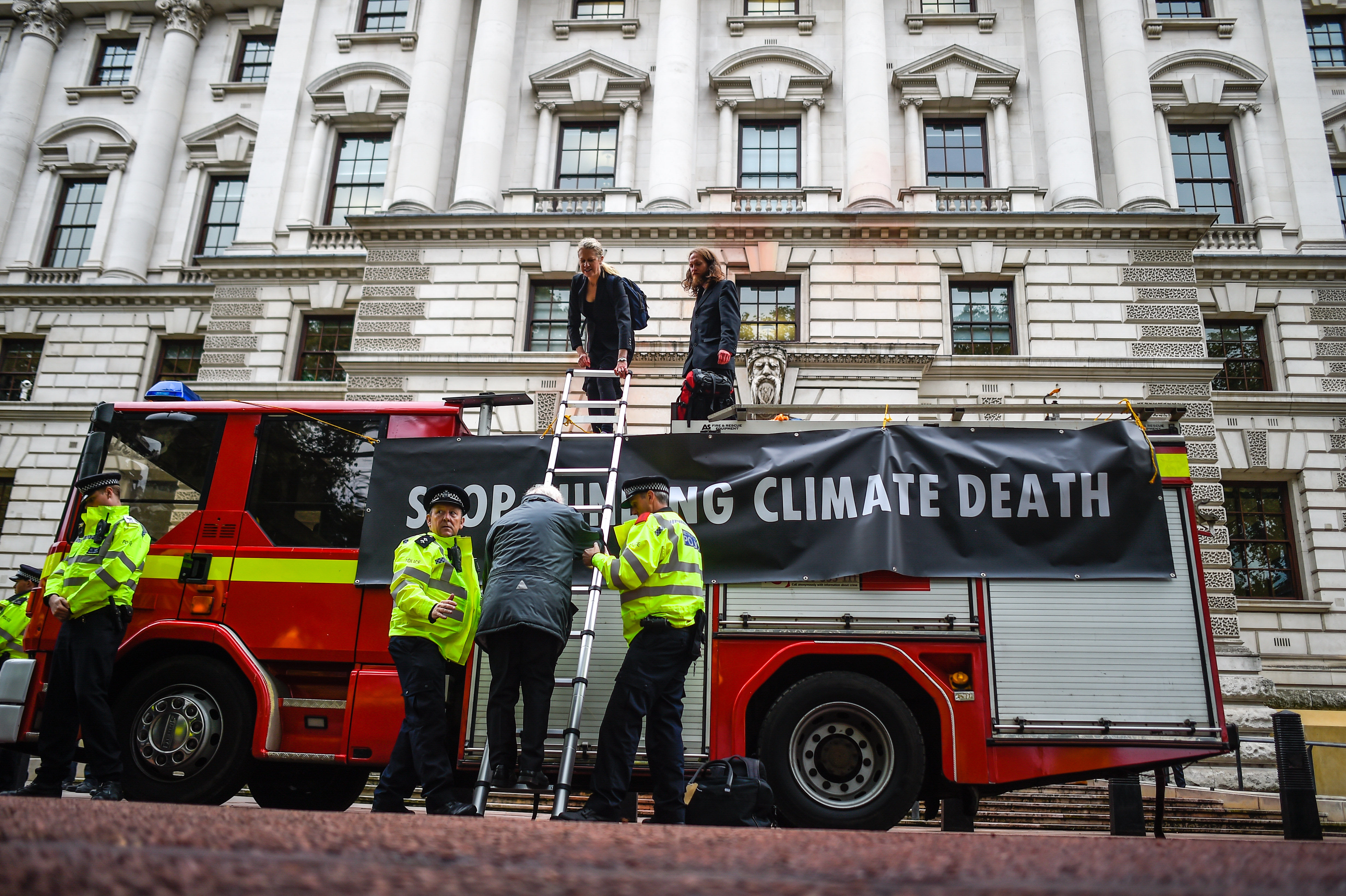 LONDON, ENGLAND - OCTOBER 03: Police officers help a climate change activist down from a fire truck outside the Treasury building on October 3, 2019 in London, England. Climate change activists from the group Extinction Rebellion used a fire engine in an attempt to spray the Treasury building. (Photo by Peter Summers/Getty Images)