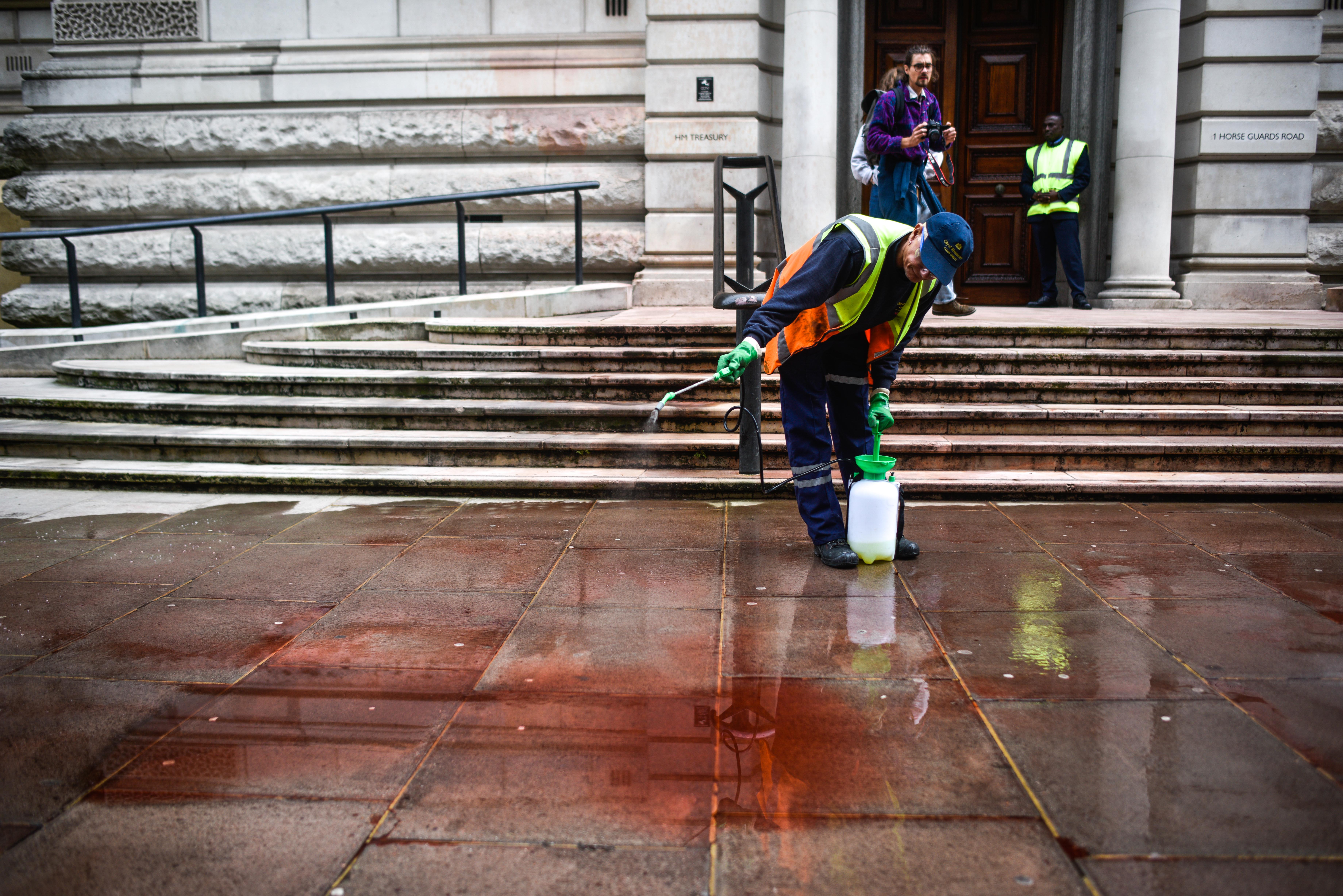 LONDON, ENGLAND - OCTOBER 03: A street worker cleans fake blood from outside the Treasury building on October 3, 2019 in London, England. Climate change activists from the group Extinction Rebellion used a fire engine in an attempt to spray the Treasury building. (Photo by Peter Summers/Getty Images)
