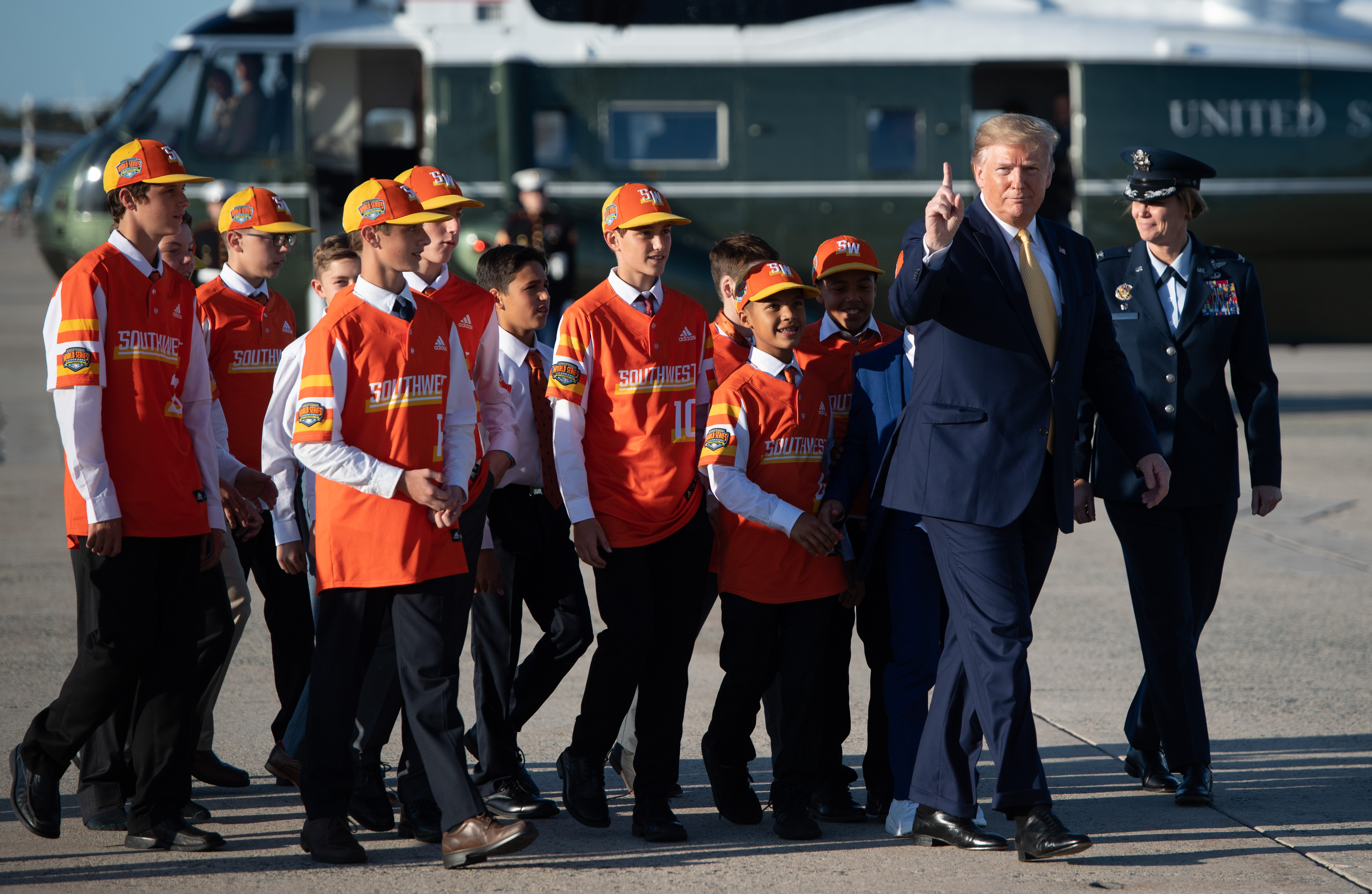 US President Donald Trump walks to board Air Force One with members of the Little League World Championship baseball team, the Eastbank All Stars of Louisiana, prior to departure from Joint Base Andrews