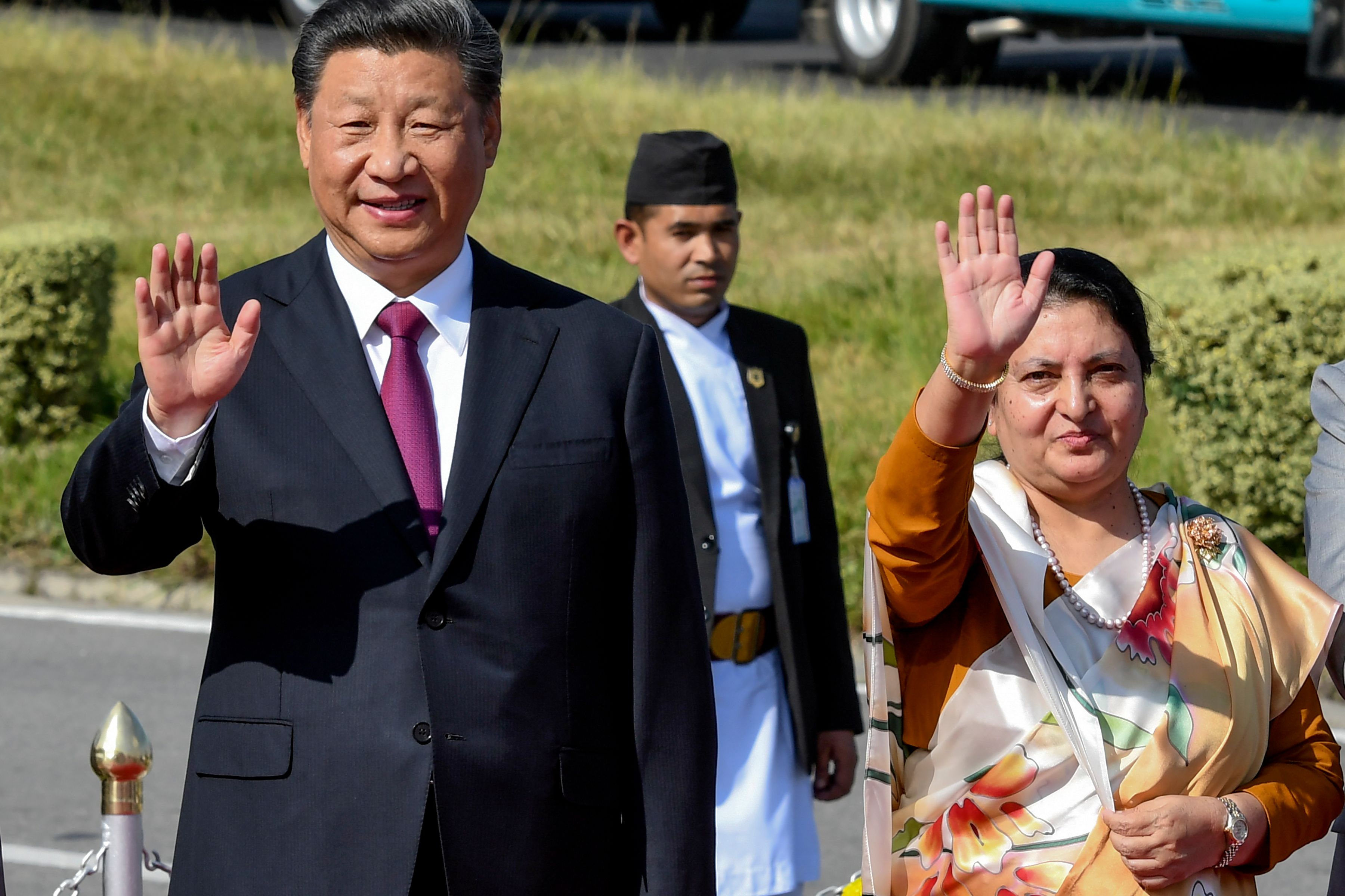Nepal's President Bidhya Devi Bhandari (R) and China's President Xi Jinping (L) wave as the latter bids farewell, wrapping up his two-day visit to Nepal, in Kathmandu on October 13, 2019. (Photo by Prakash MATHEMA / POOL / AFP via Getty Images)