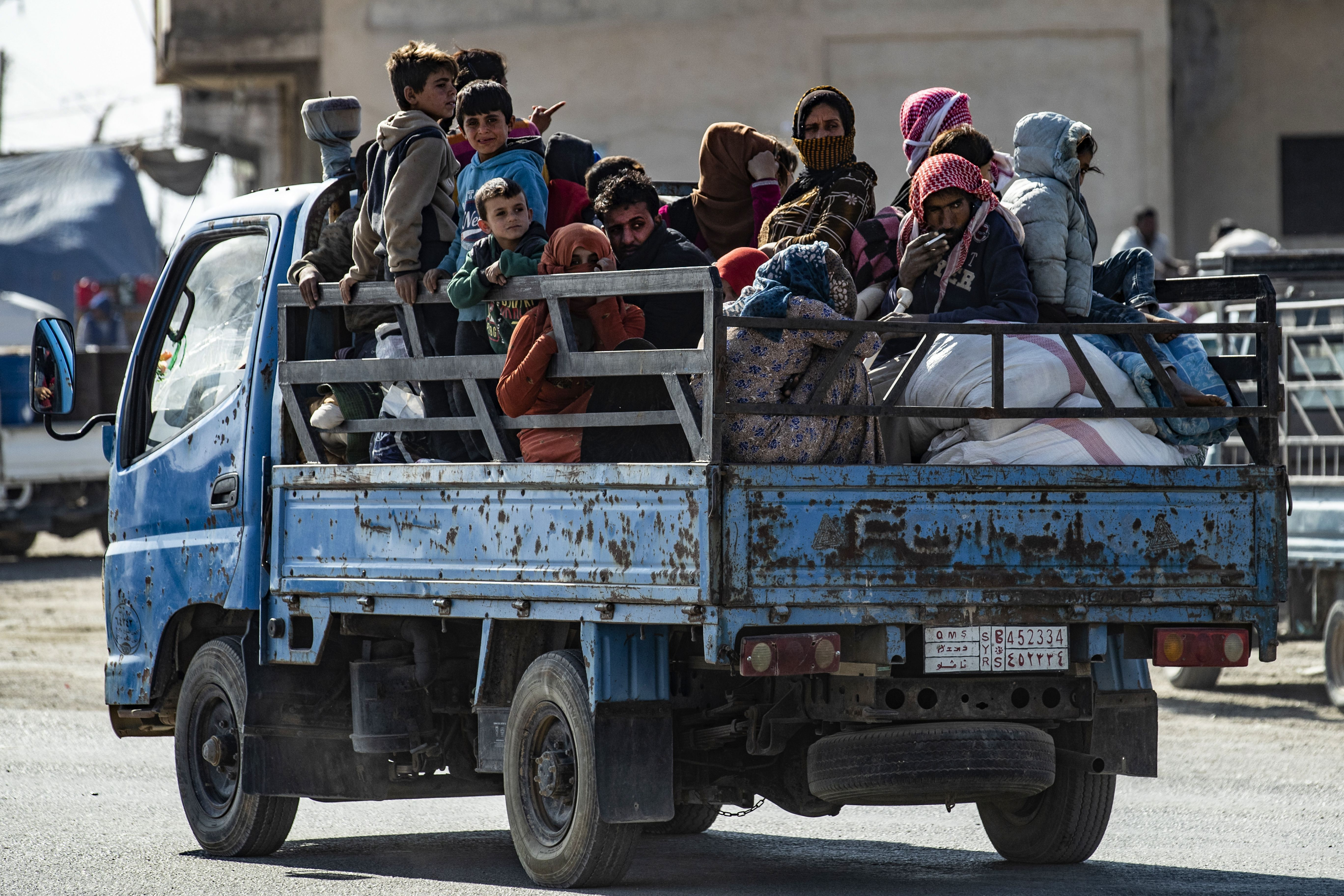 Syrian families fleeing the battle zone between Turkey-led forces and Kurdish fighters from the Syrian Democratic Forces (SDF) in and around the northern flashpoint town of Ras al-Ain on the border with Turkey, arrive along with Syrian Arab and Kurdish civilians in the city of Tal Tamr on the outskirts of Hasakeh on October 15, 2019. (DELIL SOULEIMAN/AFP via Getty Images)