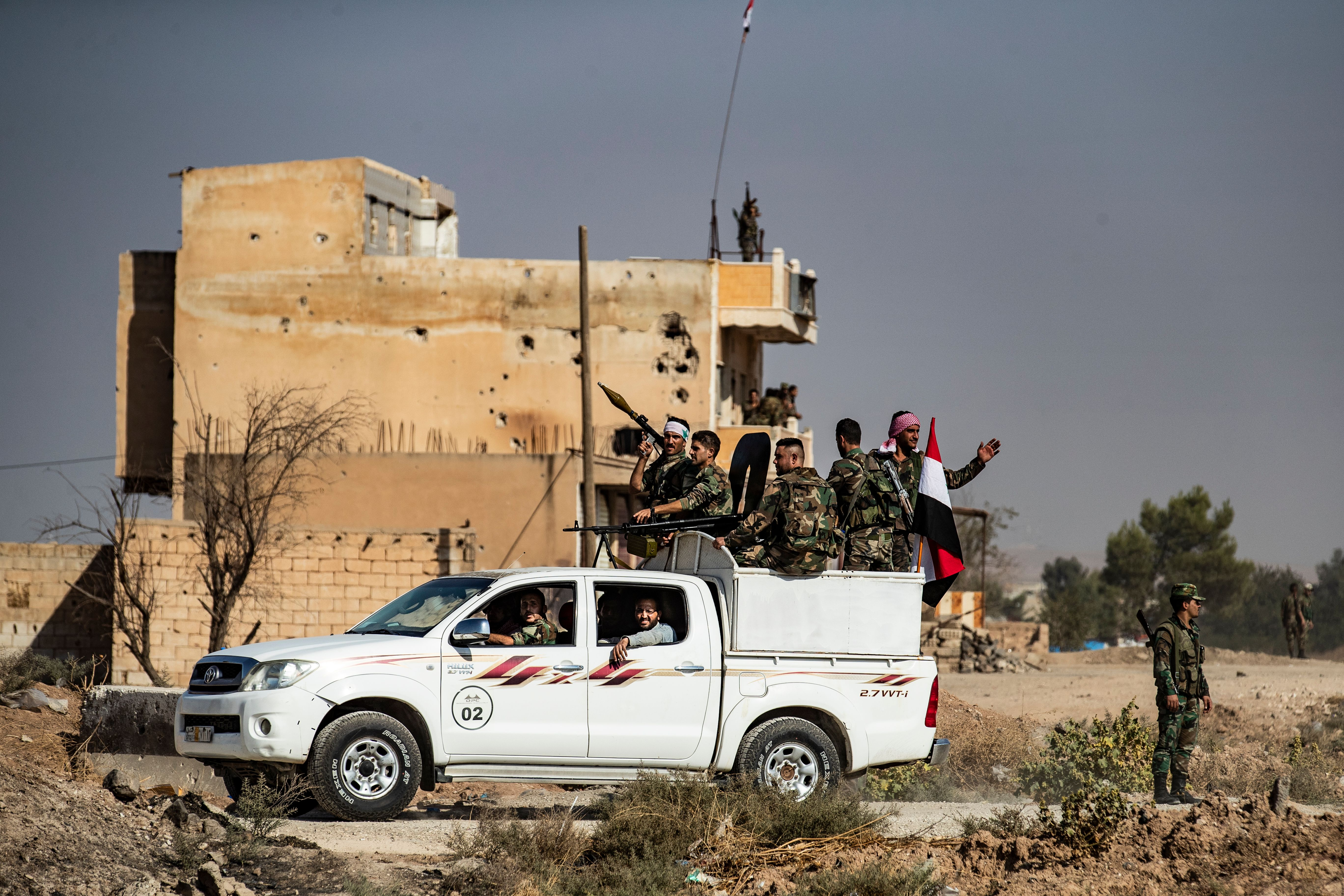 Syrian government forces arrive in the town of Tal Tamr, not far from the flashpoint Kurdish Syrian town of Ras al-Ain on the border with Turkey, which has been a key target of Turkish forces and their proxies since they launched their military assault, on October 15, 2019. - Syrian regime troops arrived after Damascus deployed troops to the country's north to contain a days-long Turkish offensive. (Photo by Delil SOULEIMAN / AFP) (Photo by DELIL SOULEIMAN/AFP via Getty Images)