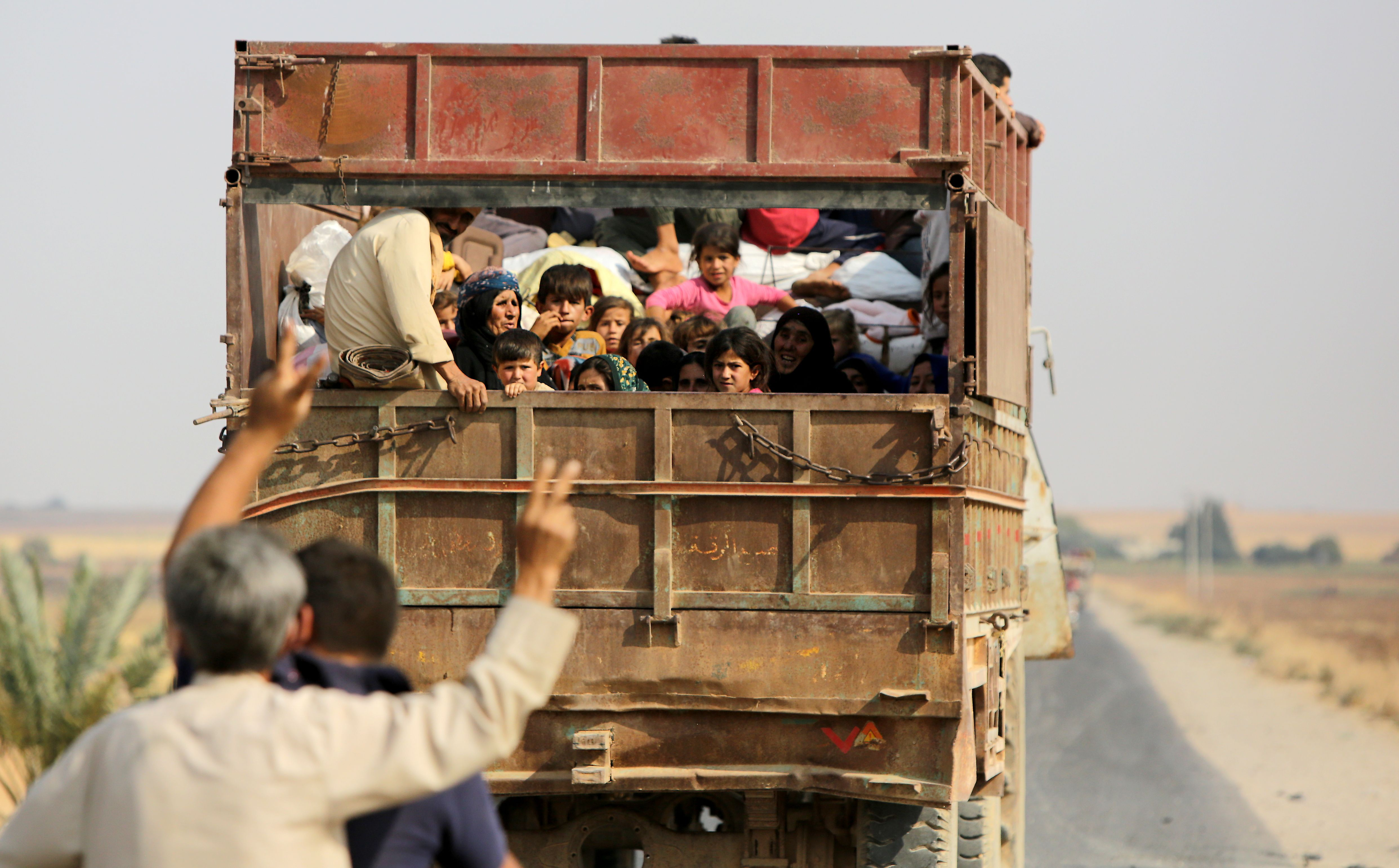 Kurdish Syrian civilians flee the town of Kobani on the Turkish border on October 16, 2019 as Turkey and its allies continue their assault on Kurdish-held border towns in northeastern Syria. (Photo by BAKR ALKASEM/AFP via Getty Images)