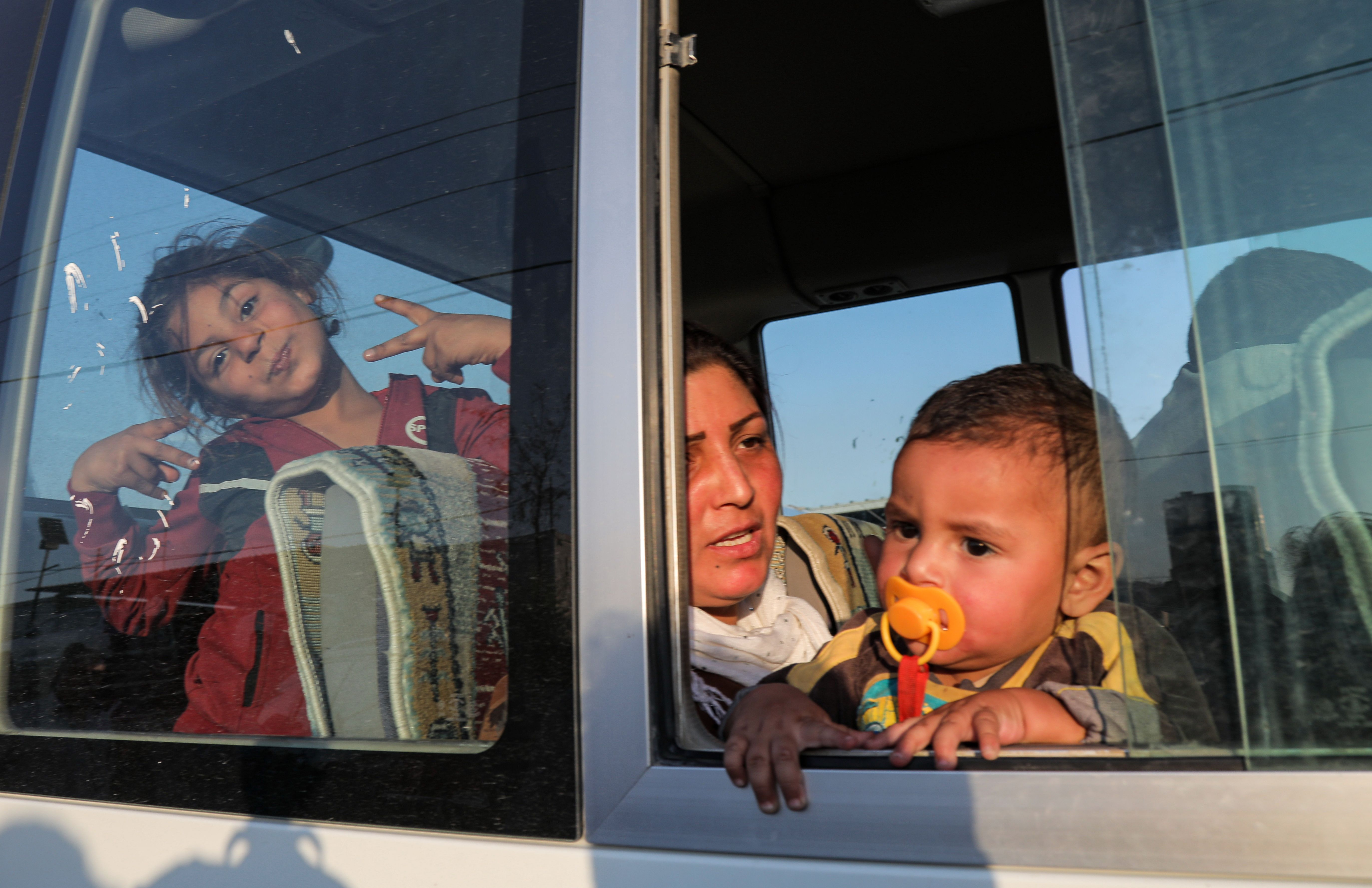 TOPSHOT - A woman holds a child while sitting in the back of a minibus transporting Syrians fleeing the ongoing Turkish military operation in northeastern Syria upon their arrival at the Bardarash camp, near the Kurdish city of Dohuk, in Iraq's autonomous Kurdish region, on October 16, 2019. - Some 500 Syrian Kurds have entered neighbouring Iraqi Kurdistan over the past four days fleeing a Turkish invasion now entering its second week, officials said. Iraqi Kurdistan previously hosted more than one million Iraqis who fled fighting with the jihadists of the Islamic State group between 2014 and 2017. (Photo by Safin HAMED / AFP) (Photo by SAFIN HAMED/AFP via Getty Images)