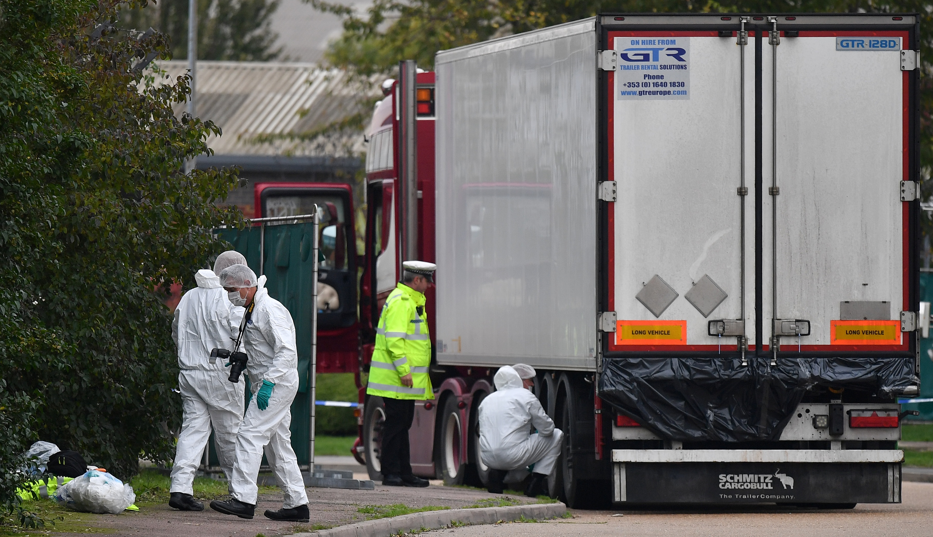 British Police forensics officers work on lorry, found to be containing 39 dead bodies, at Waterglade Industrial Park in Grays, east of London, on October 23, 2019. - Britain launched a major murder investigation after 39 bodies were found Wednesday in a truck from Bulgaria, as police tried to establish where the victims were originally from. All the victims were pronounced dead at the scene in an indusTrial park in Grays, east of London, triggering revulsion among politicians and once again putting the spotlight on the shadowy people trafficking business. (Photo by Ben STANSALL / AFP) (Photo by BEN STANSALL/AFP via Getty Images)