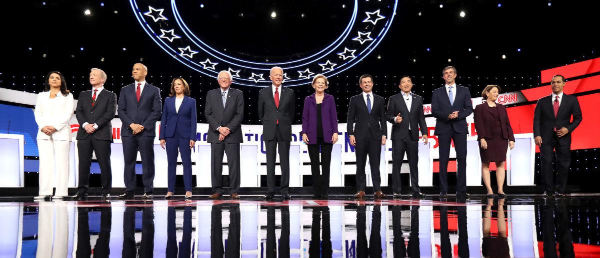 Democratic presidential candidates (L-R) Rep. Tulsi Gabbard (D-HI), billionaire Tom Steyer, Sen. Cory Booker (D-NJ), Sen. Kamala Harris (D-CA), Sen. Bernie Sanders (I-VT), former Vice President Joe Biden, Sen. Elizabeth Warren (D-MA), South Bend, Indiana Mayor Pete Buttigieg, former tech executive Andrew Yang, former Texas congressman Beto O'Rourke, Sen. Amy Klobuchar (D-MN), and former housing secretary Julian Castro at the start of the Democratic Presidential Debate at Otterbein University on October 15, 2019 in Westerville, Ohio. (Chip Somodevilla/Getty Images)