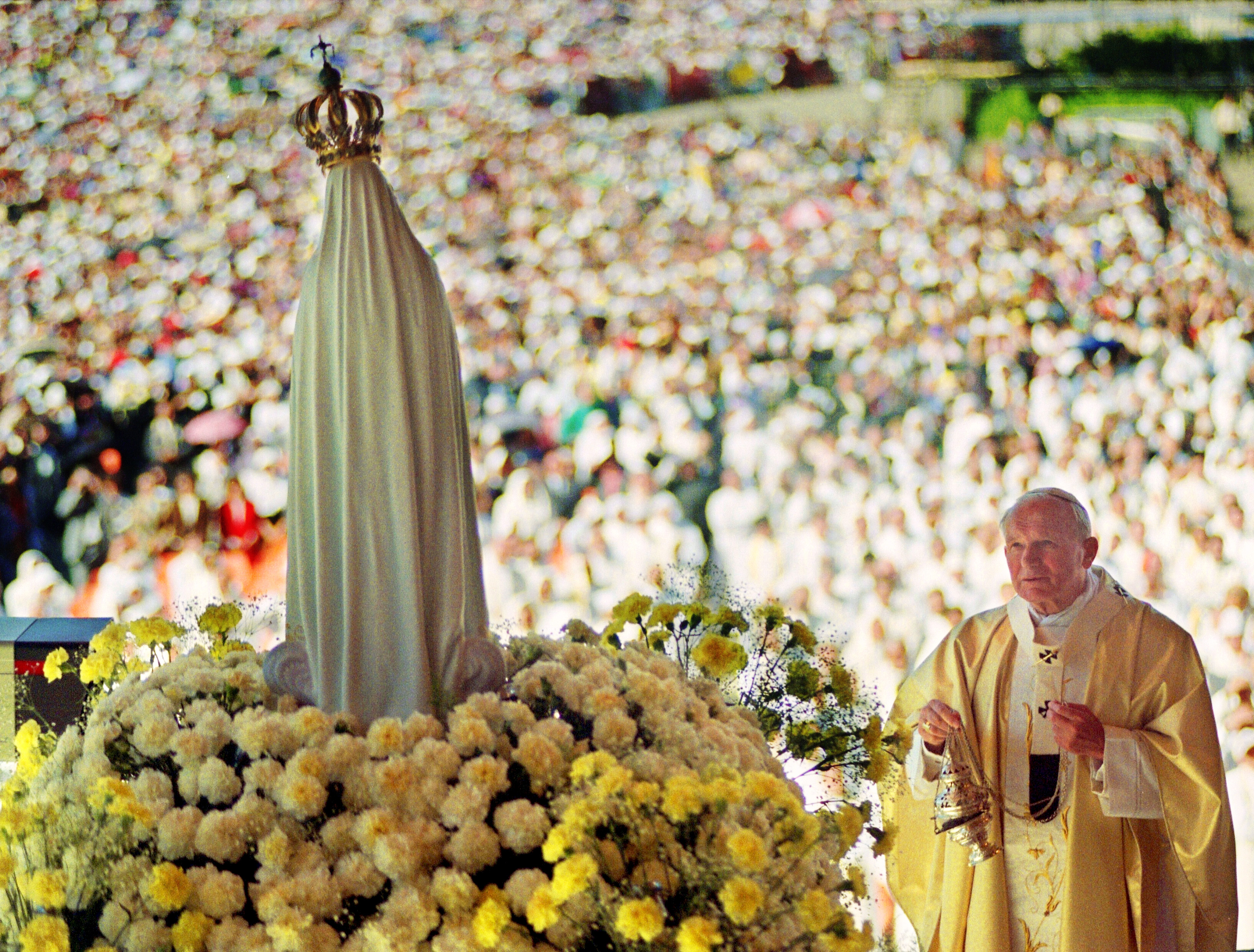 "FATIMA, PORTUGAL: Pope John Paul II celebrates a mass 12 May 1991 in the Chapel of the Apparition in front of the statue of Virgin of Fatima in Fatima where about a million believers attended the Procession of Candles. In 1997, the pope dedicated a shrine in a Polish church to the Virgin of Fatima, thanking her for intervening to save him from an assassination attempt in 1981. The Pontiff said that surviving the assassination attempt against him 13 May 1981 by Turkish terrorist Ali Agca was a miracle thanks to the ""intervention of the Virgin of Fatima"", who ""deflected the bullet"" fired at point-blank range. The Catholic church also believes the Virgin of Fatima intervened to bring an end to the Soviet regime after asking the three shepherd children to pray for the ""conversion"" of Russia. The Pontiff visited Portugal from 10 to 13 May 1991. It was his 50th International Pastoral visit. AFP PHOTO DERRICK CEYRAC . (Photo credit should read DERRICK CEYRAC/AFP via Getty Images)"