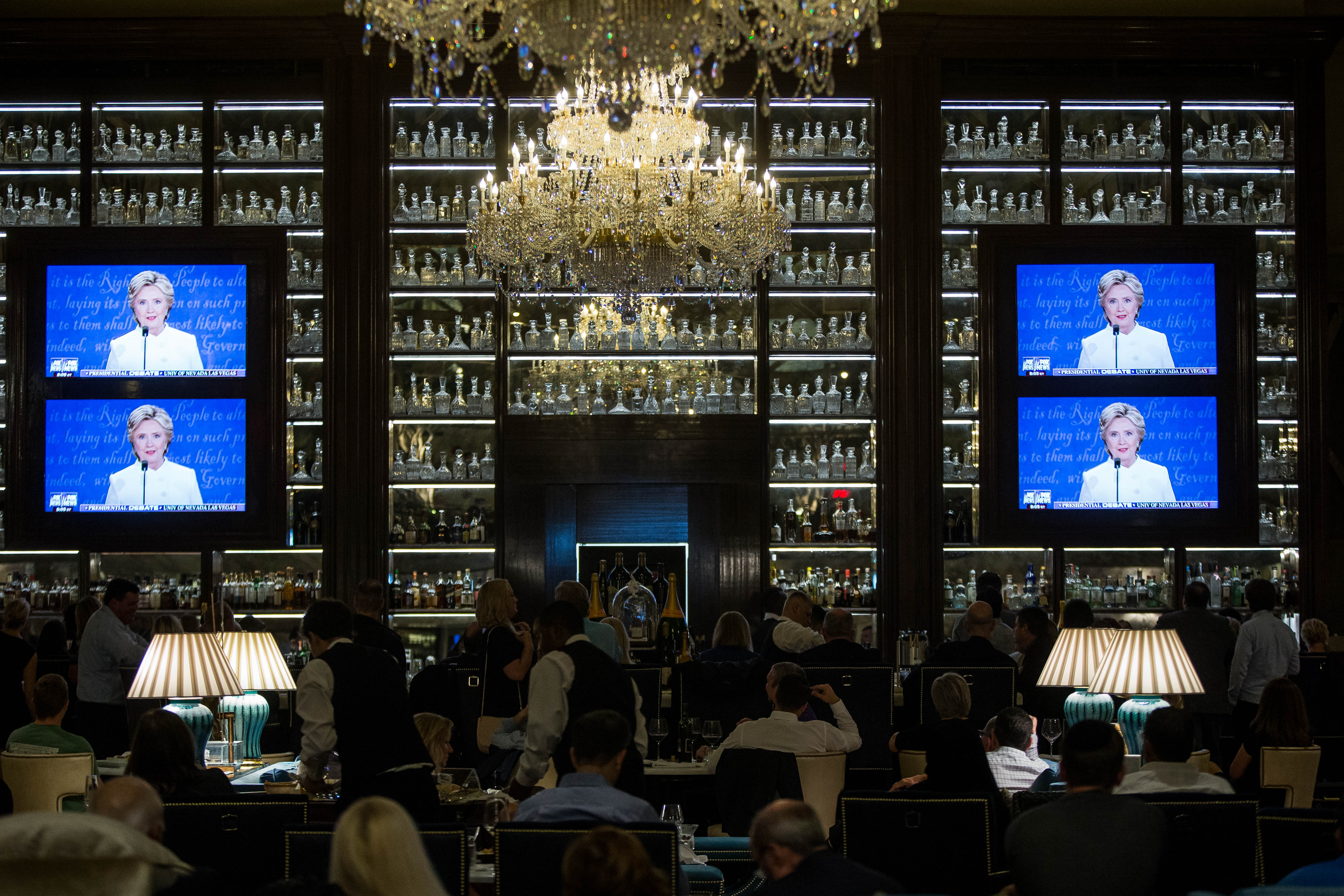 People watch the third presidential debate between presidential debate between US Democratic presidential candidate Hillary Clinton and US Republican presidential candidate Donald Trump at the Trump International Hotel October 19, 2016 in Washington, D.C. / AFP / ZACH GIBSON / Getty Images)