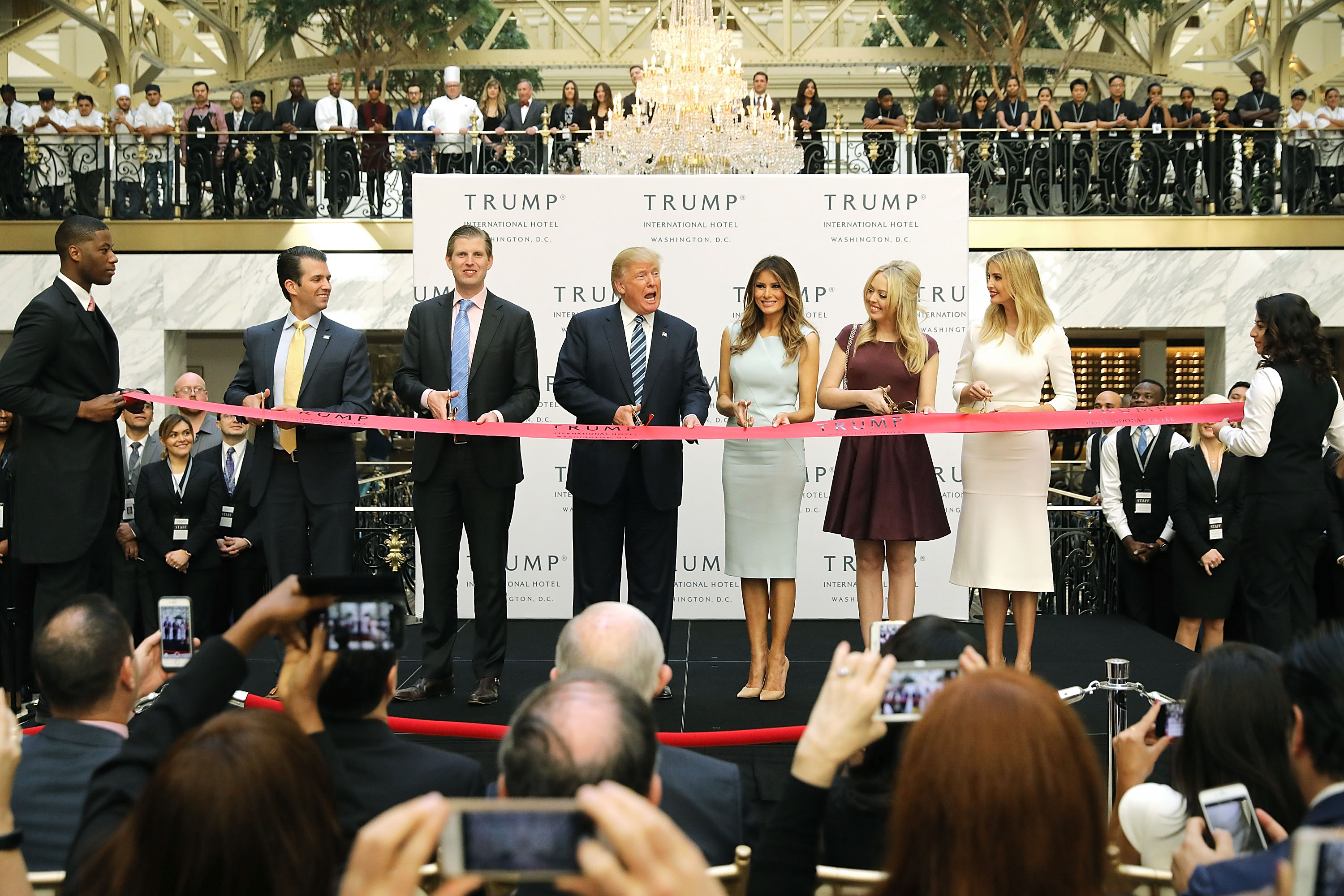 Republican presidential nominee Donald Trump (C) and his family (L-R) son Donald Trump Jr, son Eric Trummp, wife Melania Trump and daughters Tiffany Trump and Ivanka Trump cut the ribbon at the new Trump International Hotel October 26, 2016 in Washington, DC. (Photo by Chip Somodevilla/Getty Images)