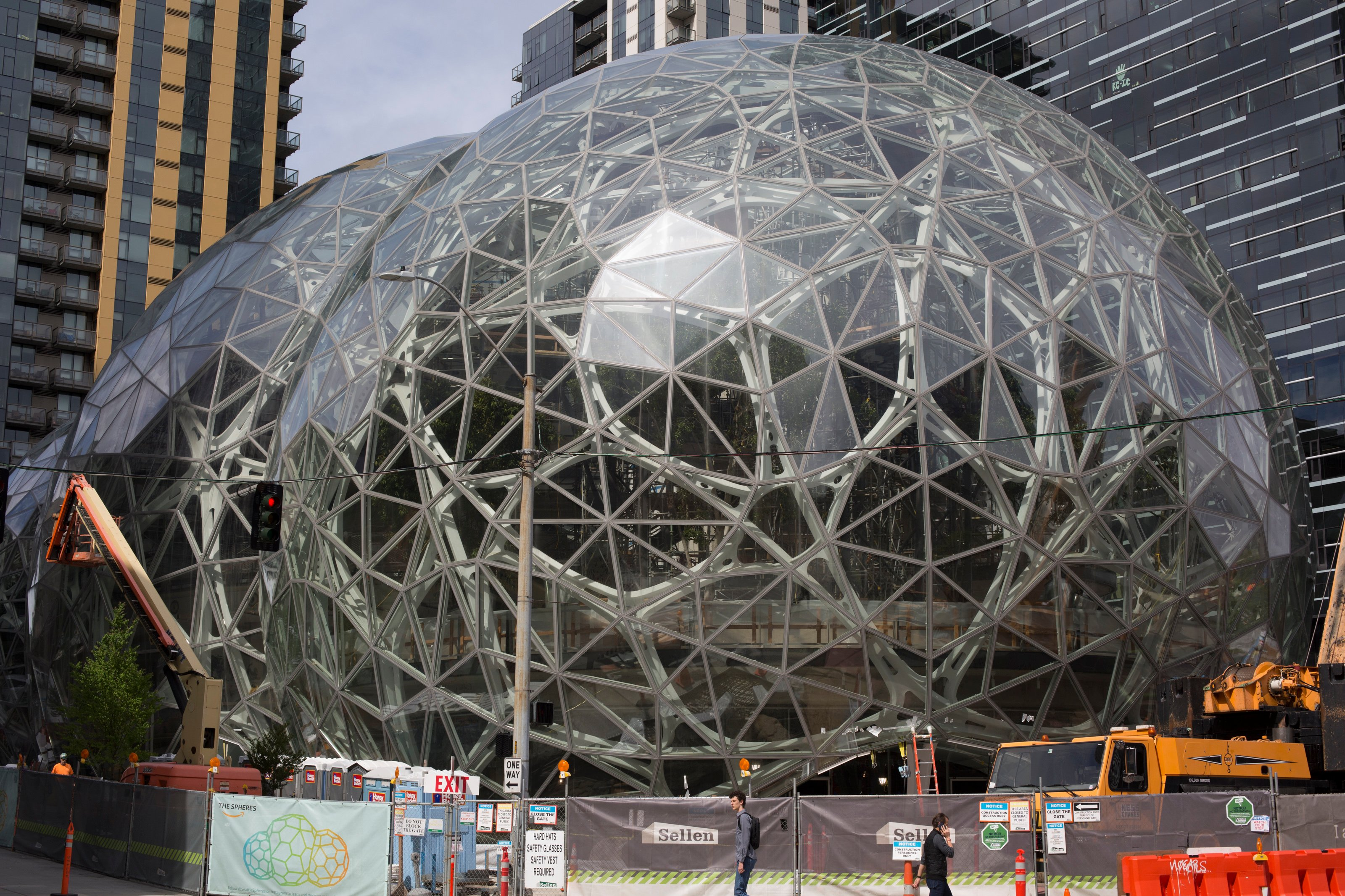 People walk past the signature glass spheres under construction at the Amazon corporate headquarters on June 16, 2017 in Seattle, Washington. (Photo by David Ryder/Getty Images)