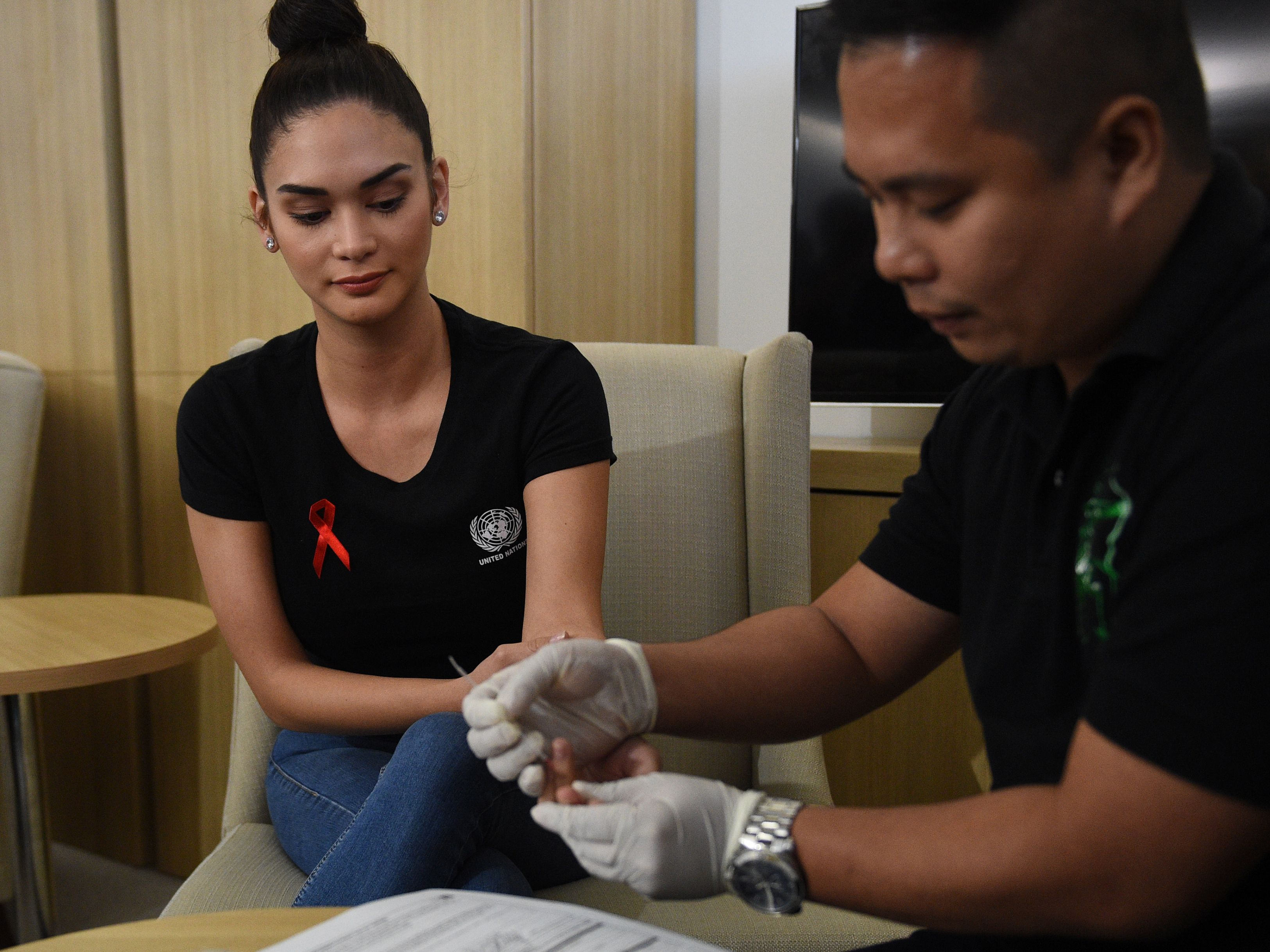 Pia Wurtzbach, The Philippines' former Miss Universe and UNAIDS goodwill ambassador for Asia, looks on as a medical worker extracts her blood sample for an HIV test at a government office in Taguig City, suburban Manila on August 9, 2017. (TED ALJIBE/AFP/Getty Images)