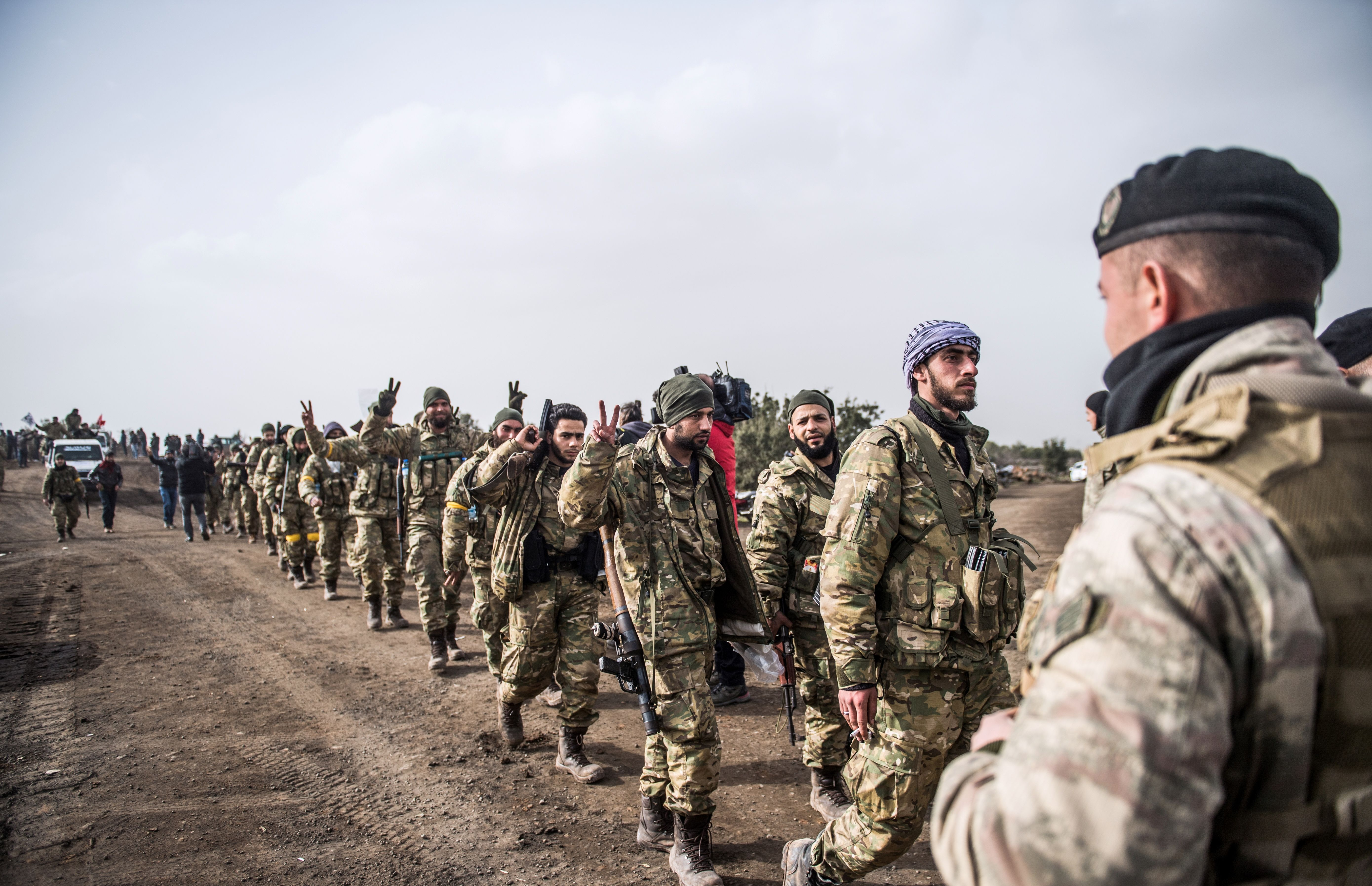 Syrian opposition fighters walk through Syria in front of Turkish troops near the Syrian border at Hassa, Hatay province, on January 22, 2018. (Photo credit should read BULENT KILIC/AFP/Getty Images)