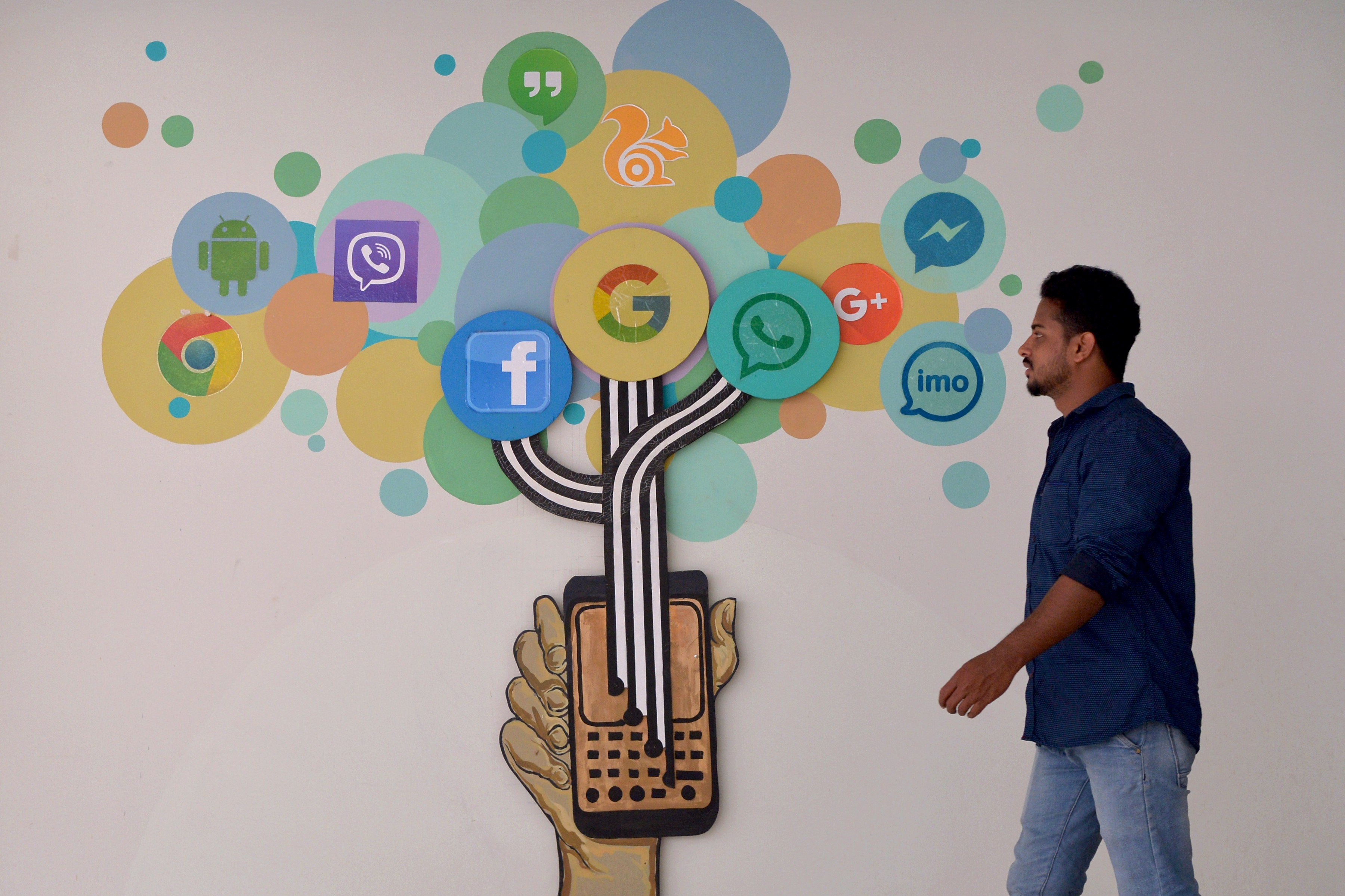An Indian visitor passes a mural depicting various social medias including Facebook, inside a building in Bangalore on March 22, 2018. (Photo credit should read MANJUNATH KIRAN/AFP/Getty Images)