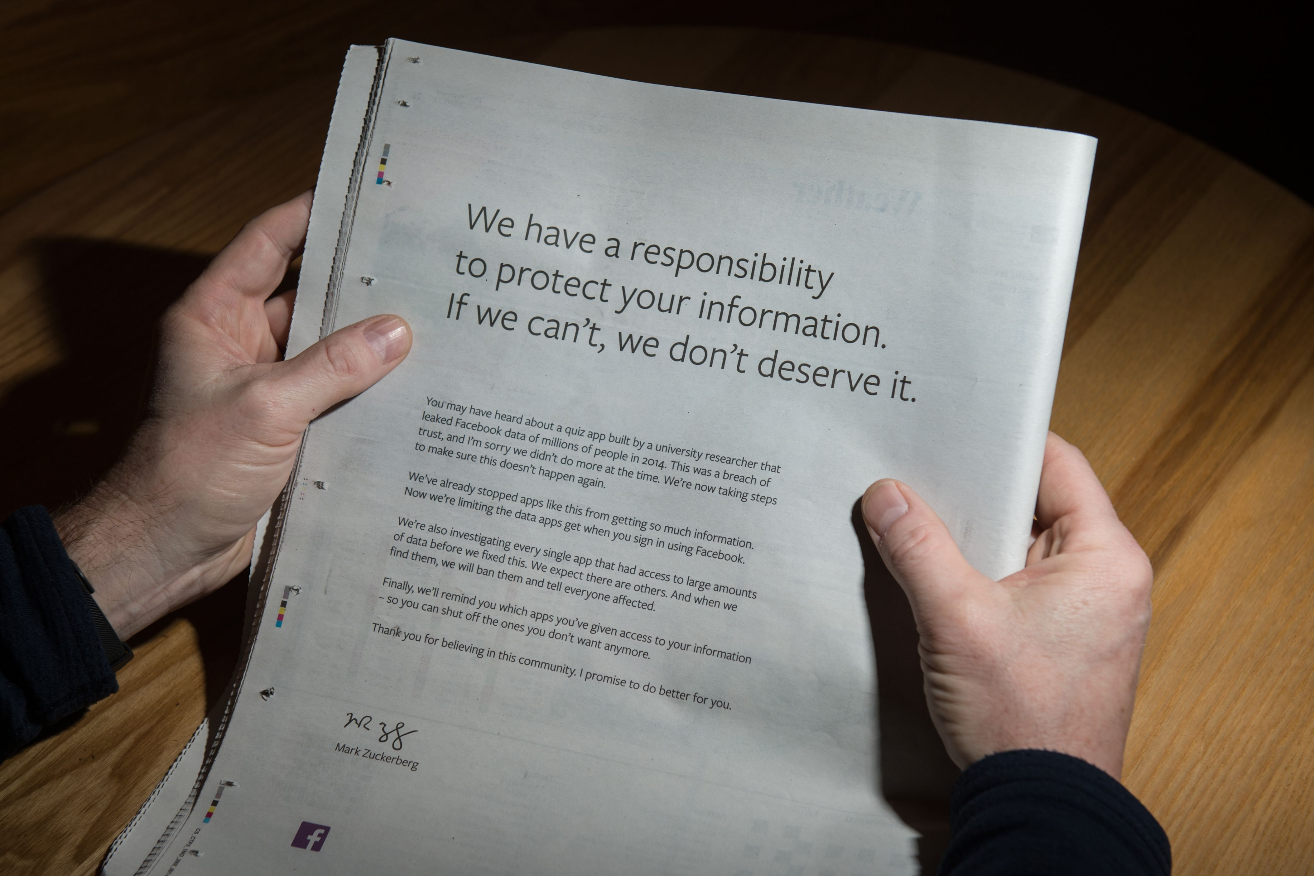 A man reads a full-page advertisment, taken out by Mark Zuckerberg, the chairman and chief executive officer of Facebook to apologise for the large-scale leak of personal data from the social network, on the backpage of a newspaper, in Ripon, England on March 25, 2018. Facebook chief Mark Zuckerberg took out full-page ads in almost all of Britain's national newspapers on March 25, 2018, to apologise for a huge data privacy scandal. / AFP PHOTO / Oli SCARFF