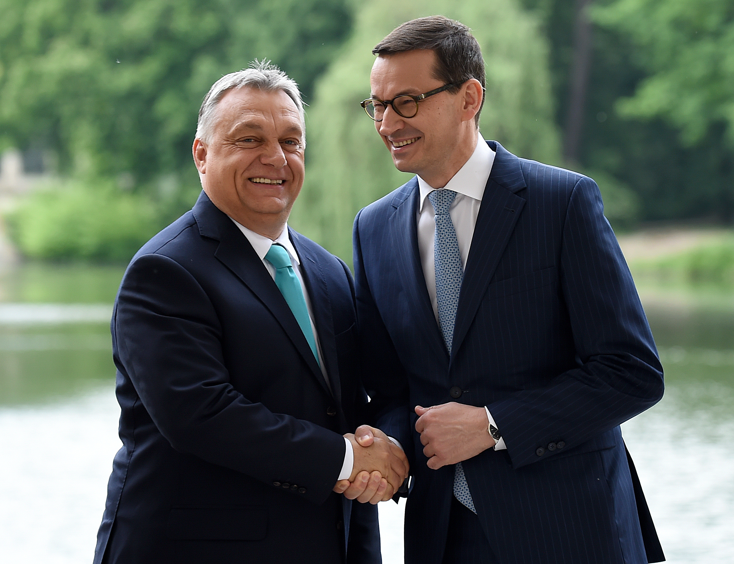 Polish Prime Minister Mateusz Morawiecki shakes hands with Hungarian Prime Minister Viktor Orban (L) during a meeting on May 14, 2018 at the Palace on the Isle in Warsaw's Lazienki Park. (Photo by JANEK SKARZYNSKI / AFP) (Photo credit should read JANEK SKARZYNSKI/AFP/Getty Images)