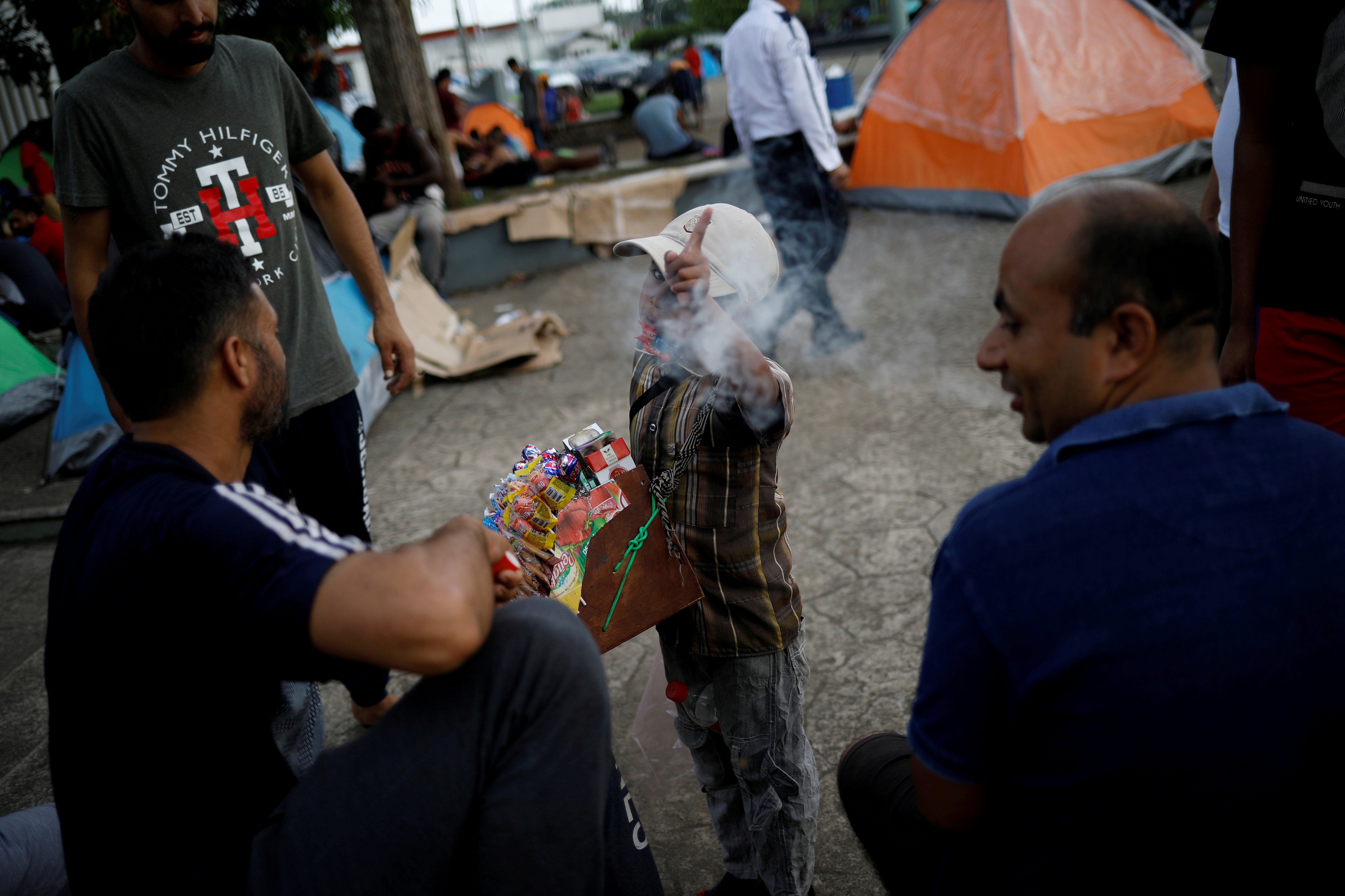 FILE PHOTO: A boy selling candies and cigarettes gestures to the camera as he argues with migrants from India outside of Siglo XXI migration facility in Tapachula