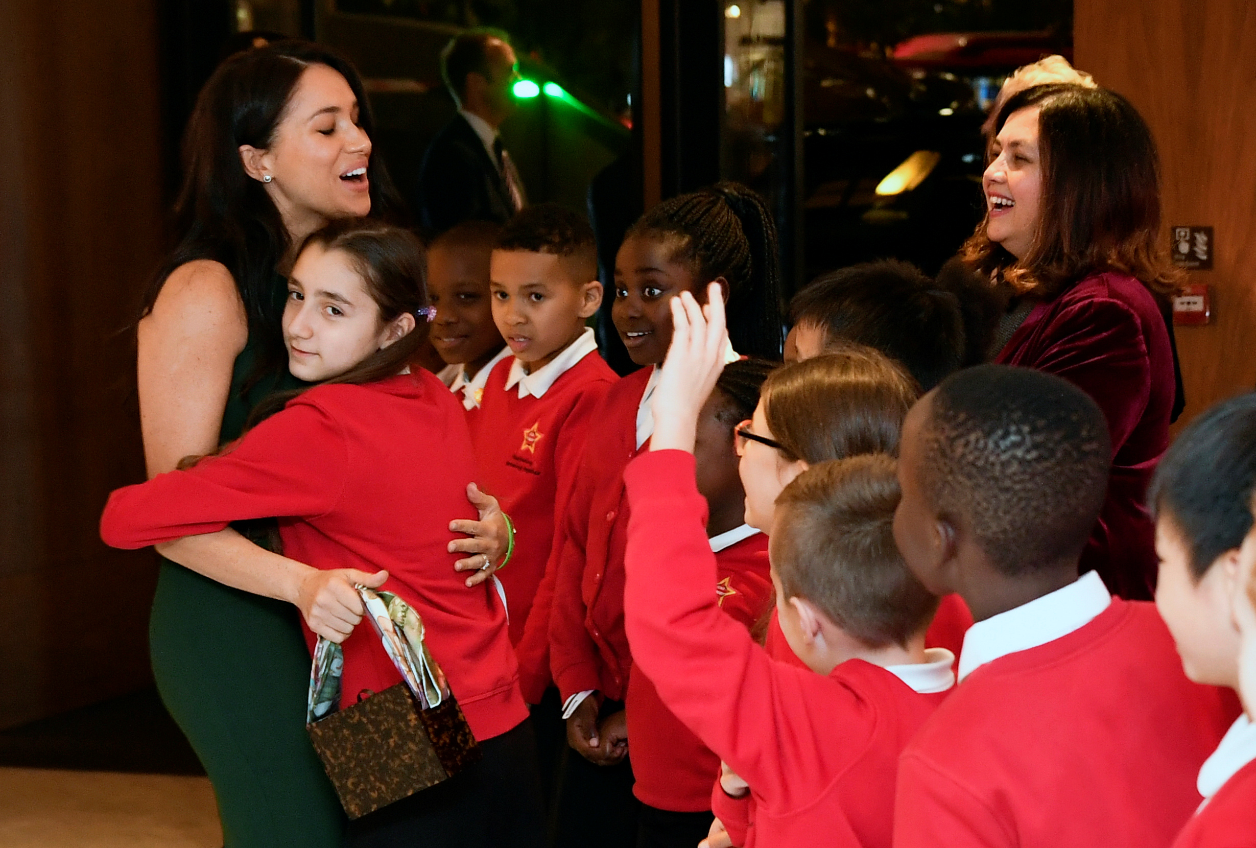 Meghan, Duchess of Sussex (L) is embraced by a member of Star Primary School Choir during the annual WellChild Awards in London on October 15, 2019. - WellChild is the national charity for seriously ill children and their families. The WellChild Awards celebrate the inspiring qualities of some of the country's seriously ill young people and the dedication of those who care for and support them. (Photo by TOBY MELVILLE/POOL/AFP via Getty Images)