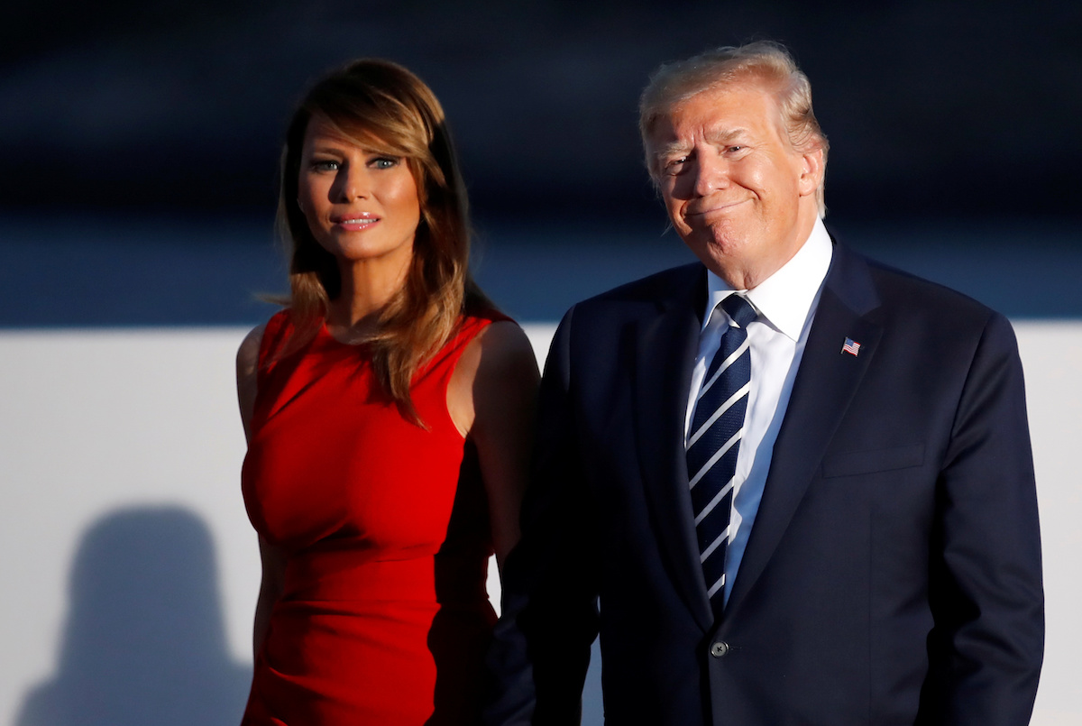 U.S. President Donald Trump and first lady Melania Trump smile during the family photo session with invited guests at the G7 summit in Biarritz, France August 25, 2019. REUTERS/Christian Hartmann/Pool