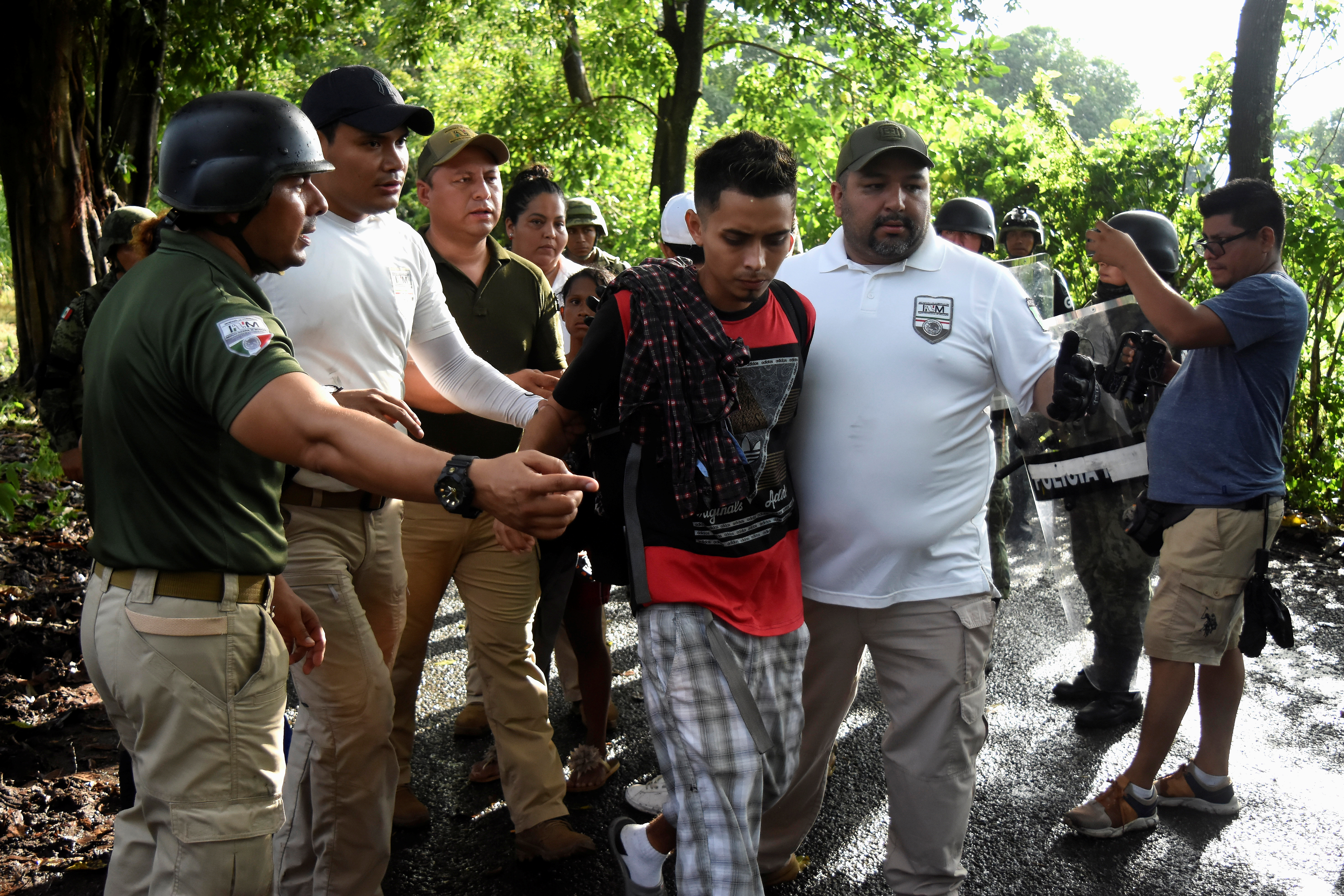Agents of the National Migration Institute (INM) detain a migrant during an operation by the National Guard to halt a caravan of migrants from Africa, the Caribbean and Central America, hours after they embarked toward the United States, in Tuzantan