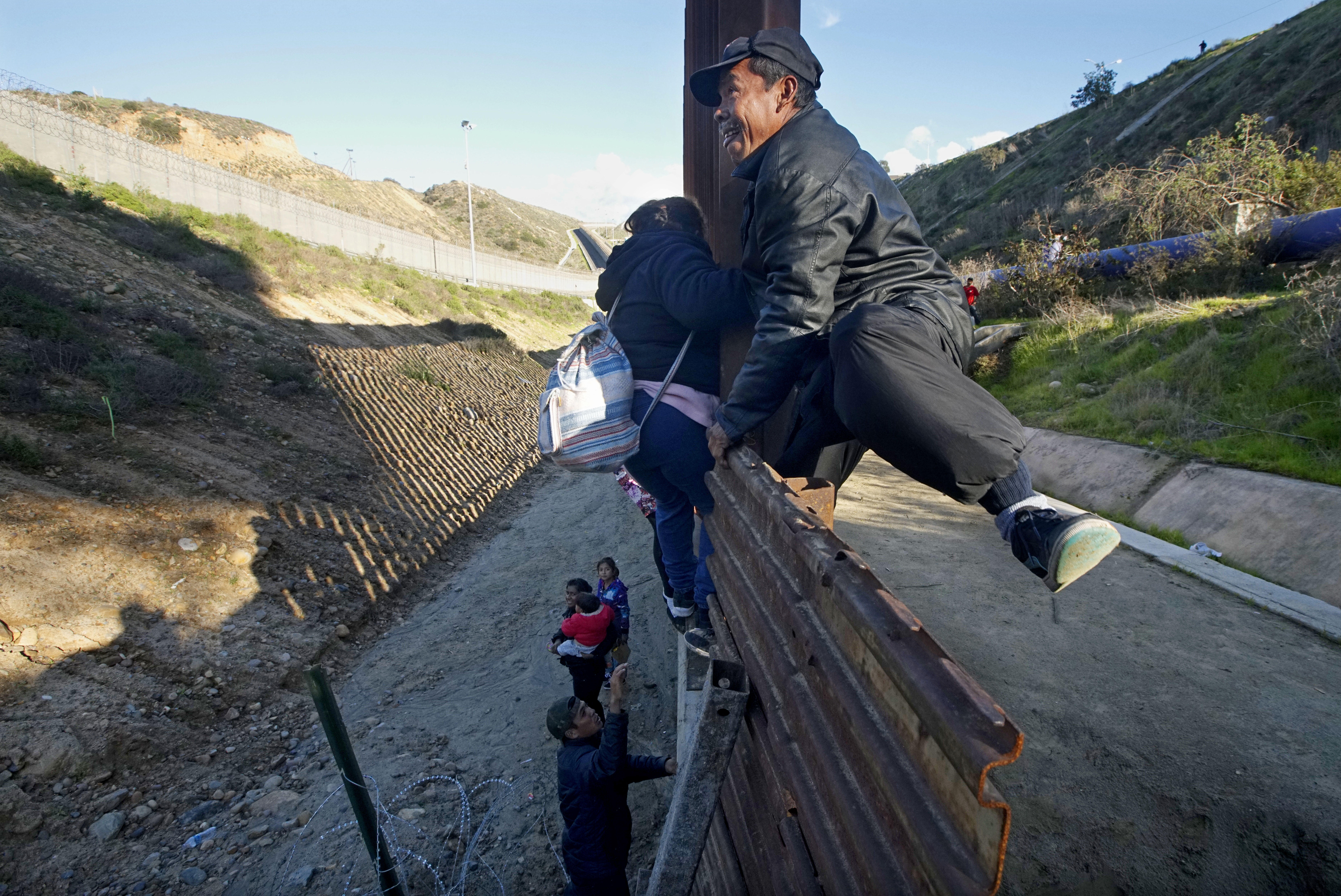 Honduran migrants climb over a border fence in Tijuana, Mexico on January 6, 2019. (Sandy Huffaker/Getty Images)
