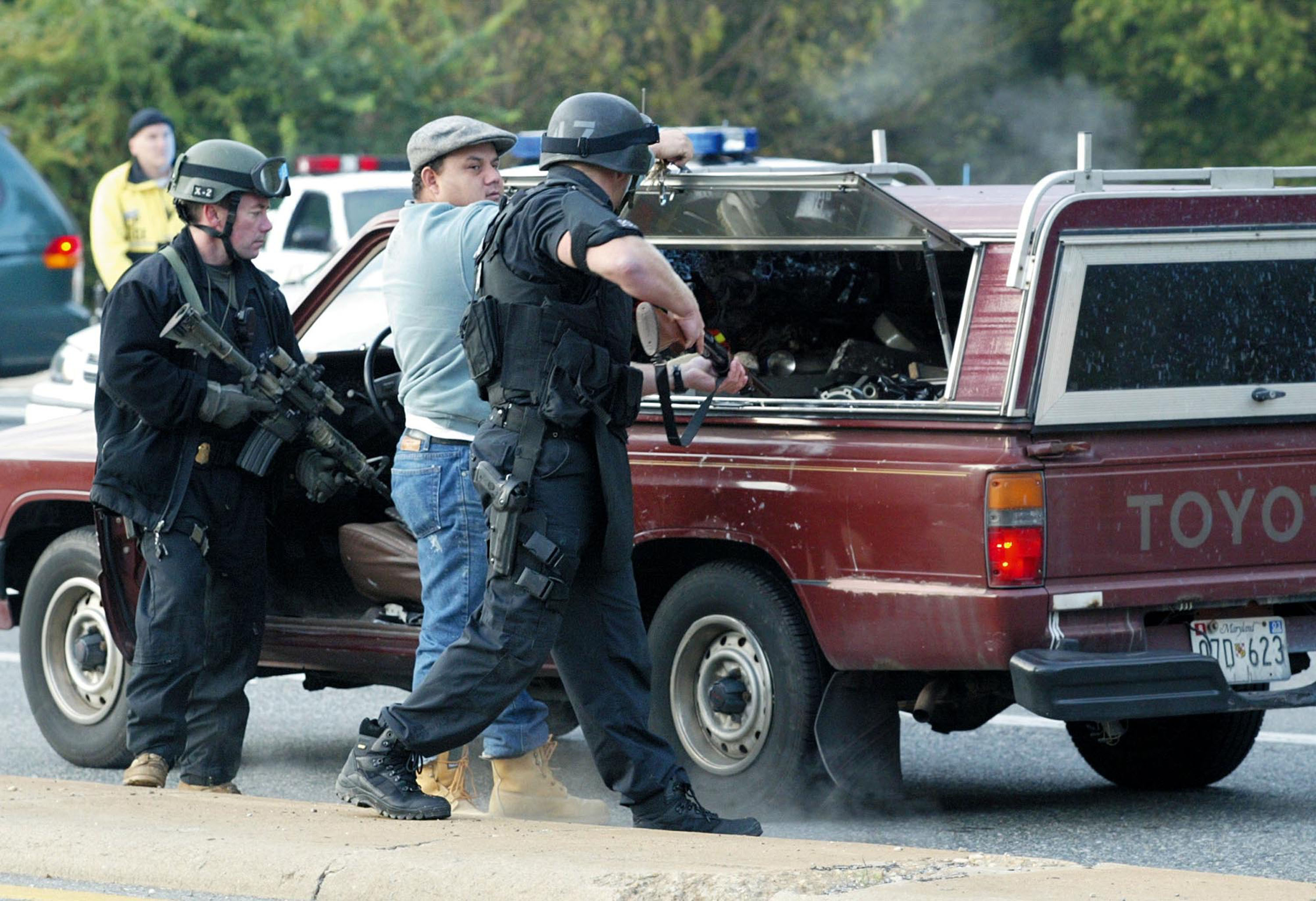 Police search a pickup truck about one mile south from the scene where the D.C. snipers shot a bus driver in Aspen Hill, Maryland on October 22, 2002. (Alex Wong/Getty Images)