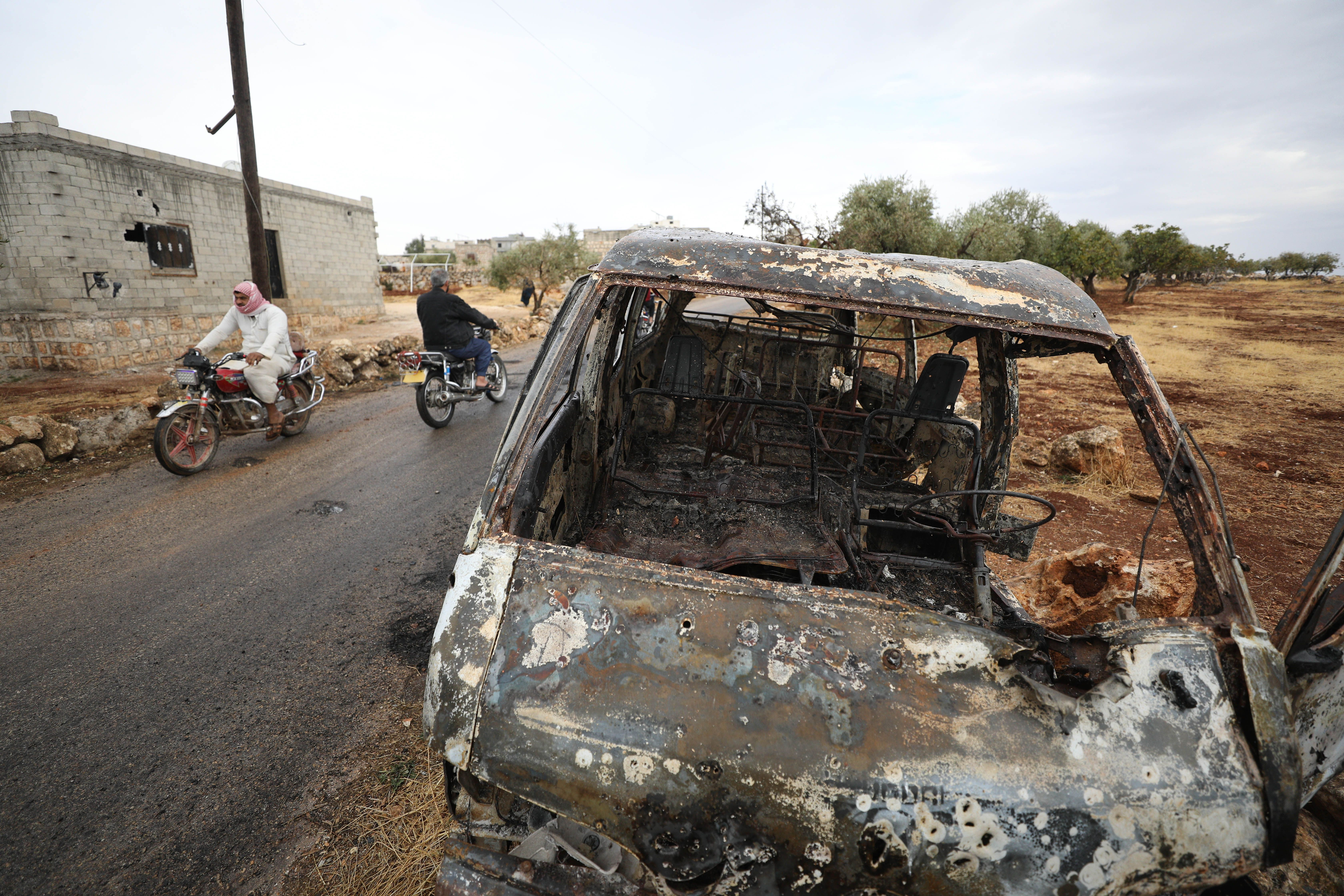 A picture taken on October 28, 2019 shows Syrian bikers riding past a damaged car at the site of a suspected US-led operation against Islamic State (IS) chief Abu Bakr al-Baghdadi the previous day, on the edge of the small Syrian village of Barisha in the country's opposition-held northwestern Idlib province. - US President Donald Trump announced that Baghdadi, the elusive leader of the jihadist group and the world's most wanted man, was killed in the early hours of Octobe 27 in an overnight US raid near the village, located less than five kilometres from Turkey and controlled by the dominant jihadist group Hayat Tahrir al-Sham, an organisation that includes former operatives from Al-Qaeda's Syria affiliate. (Photo by Omar HAJ KADOUR / AFP) (Photo by OMAR HAJ KADOUR/AFP via Getty Images)