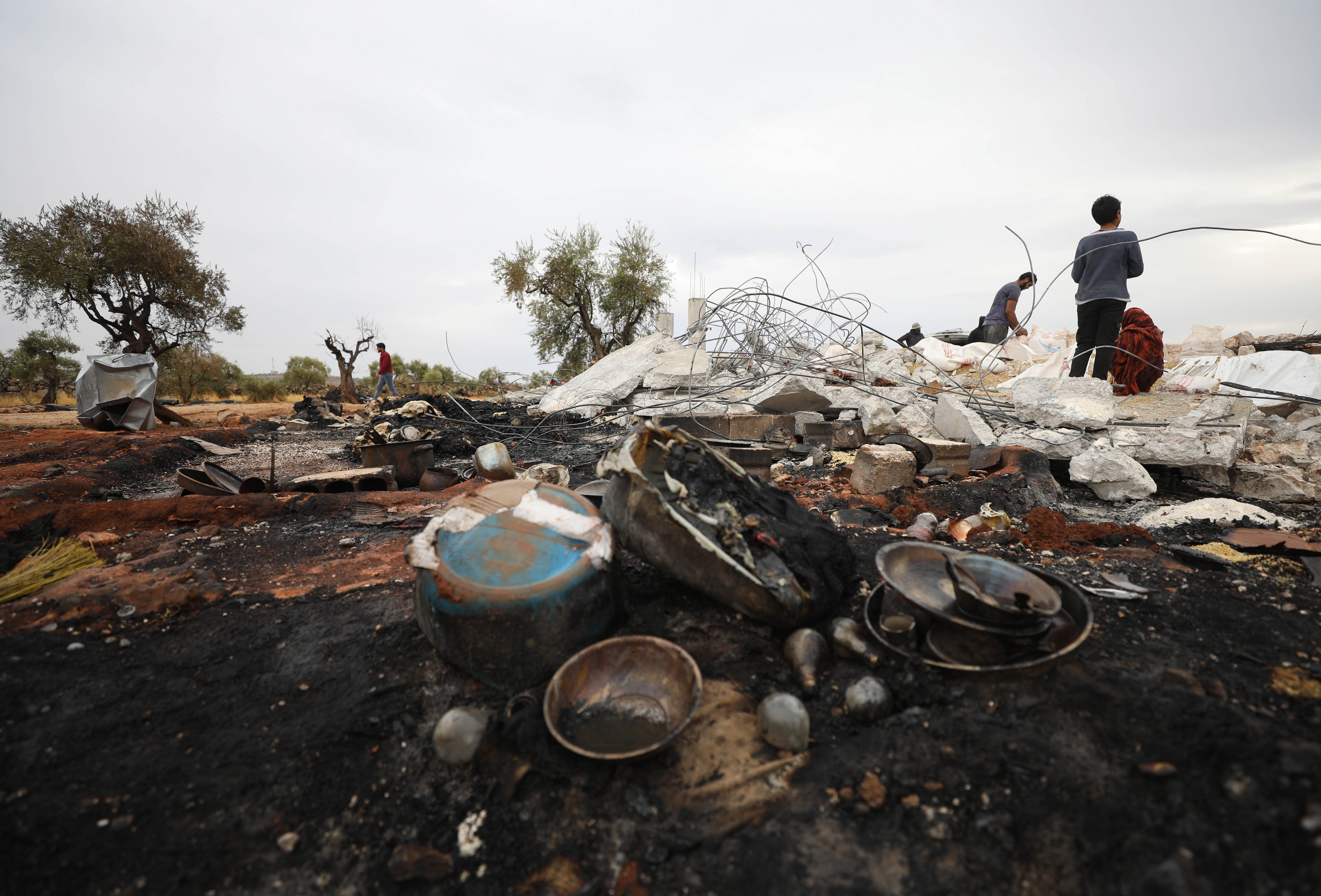 A picture taken on October 28, 2019 shows Syrians sifting through the rubble at the site of a suspected US-led operation against Islamic State (IS) chief Abu Bakr al-Baghdadi the previous day, on the edge of the small Syrian village of Barisha in the country's opposition-held northwestern Idlib province. - US President Donald Trump announced that Baghdadi, the elusive leader of the jihadist group and the world's most wanted man, was killed in the early hours of Octobe 27 in an overnight US raid near the village, located less than five kilometres from Turkey and controlled by the dominant jihadist group Hayat Tahrir al-Sham, an organisation that includes former operatives from Al-Qaeda's Syria affiliate. (Photo by Omar HAJ KADOUR / AFP) (Photo by OMAR HAJ KADOUR/AFP via Getty Images)