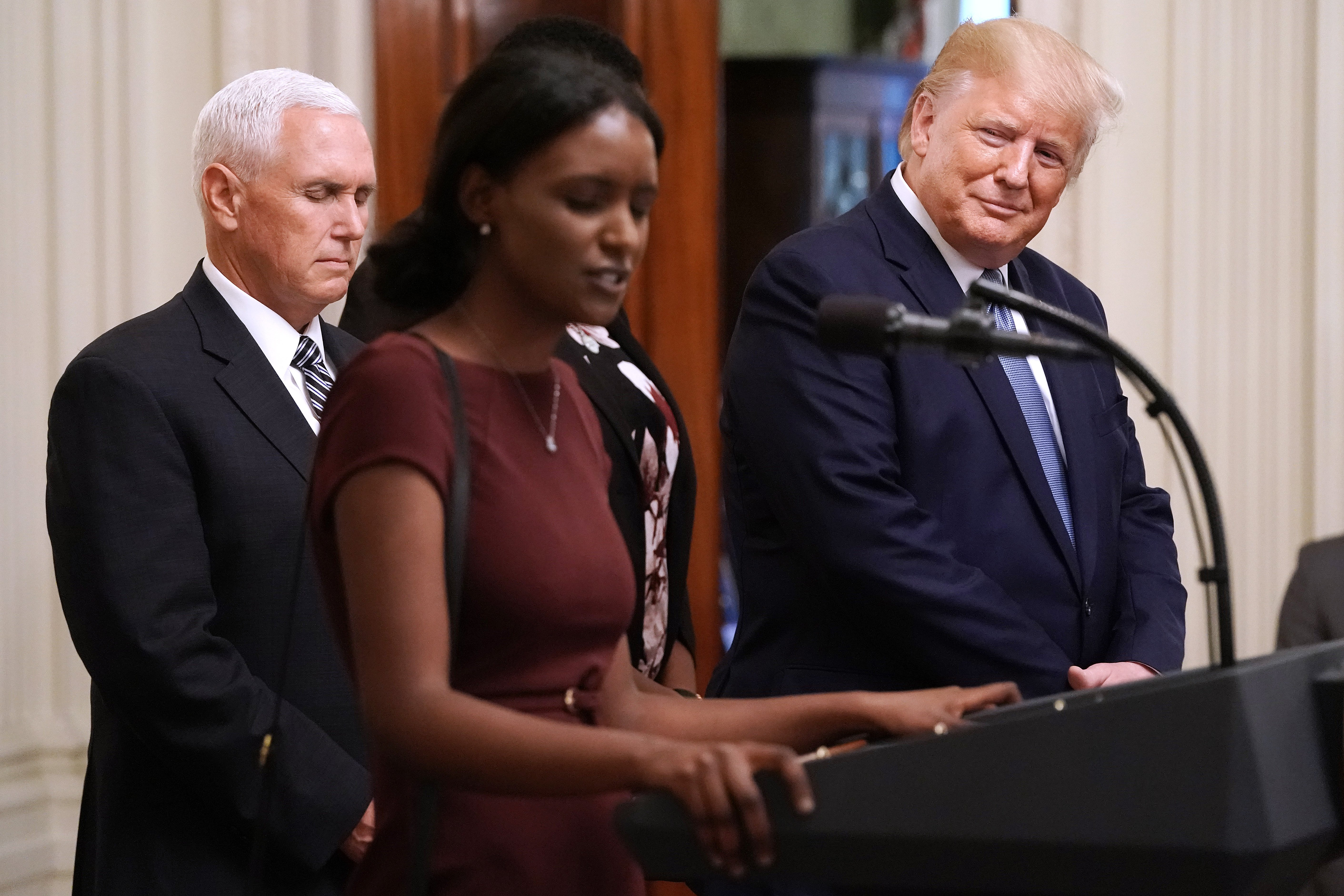 President Donald Trump (R) listens as a woman he invited on stage prays with Vice President Mike Pence during an event for the Young Black Leadership Summit in the East Room of the White House October 04, 2019 in Washington, DC. Organized by the conservative nonprofit political group Turning Points USA, the summit bills itself as a professional development, leadership training and networking opportunity. Chip Somodevilla/Getty Images