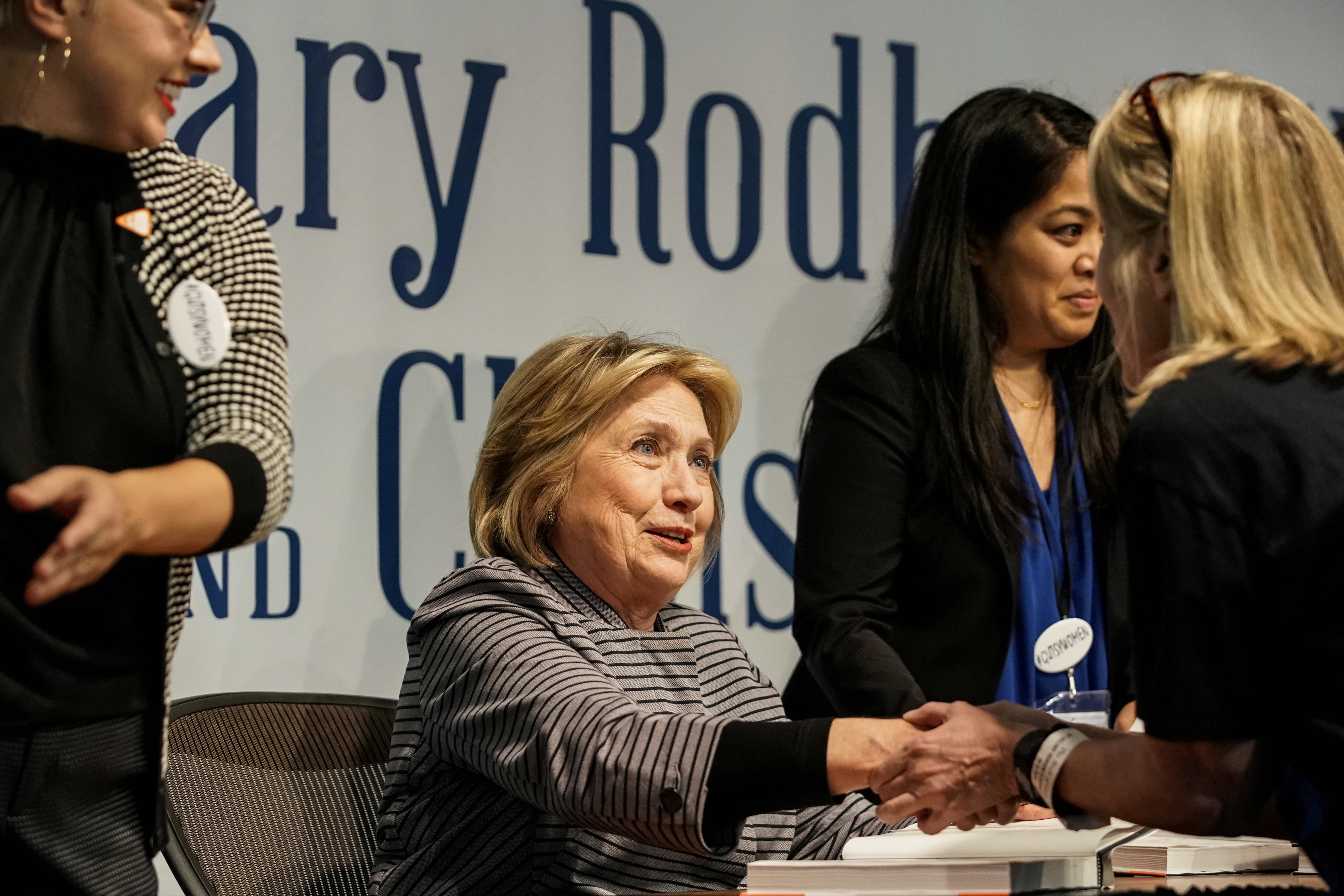 """FILE PHOTO: Hillary Clinton talks to a supporter during a signing event for """"The Book of Gutsy Women"""", a book by her and her daughter Chelsea Clinton, in the Manhattan borough of New York City, New York, U.S., October 3, 2019. REUTERS/Jeenah Moon/File Photo"""
