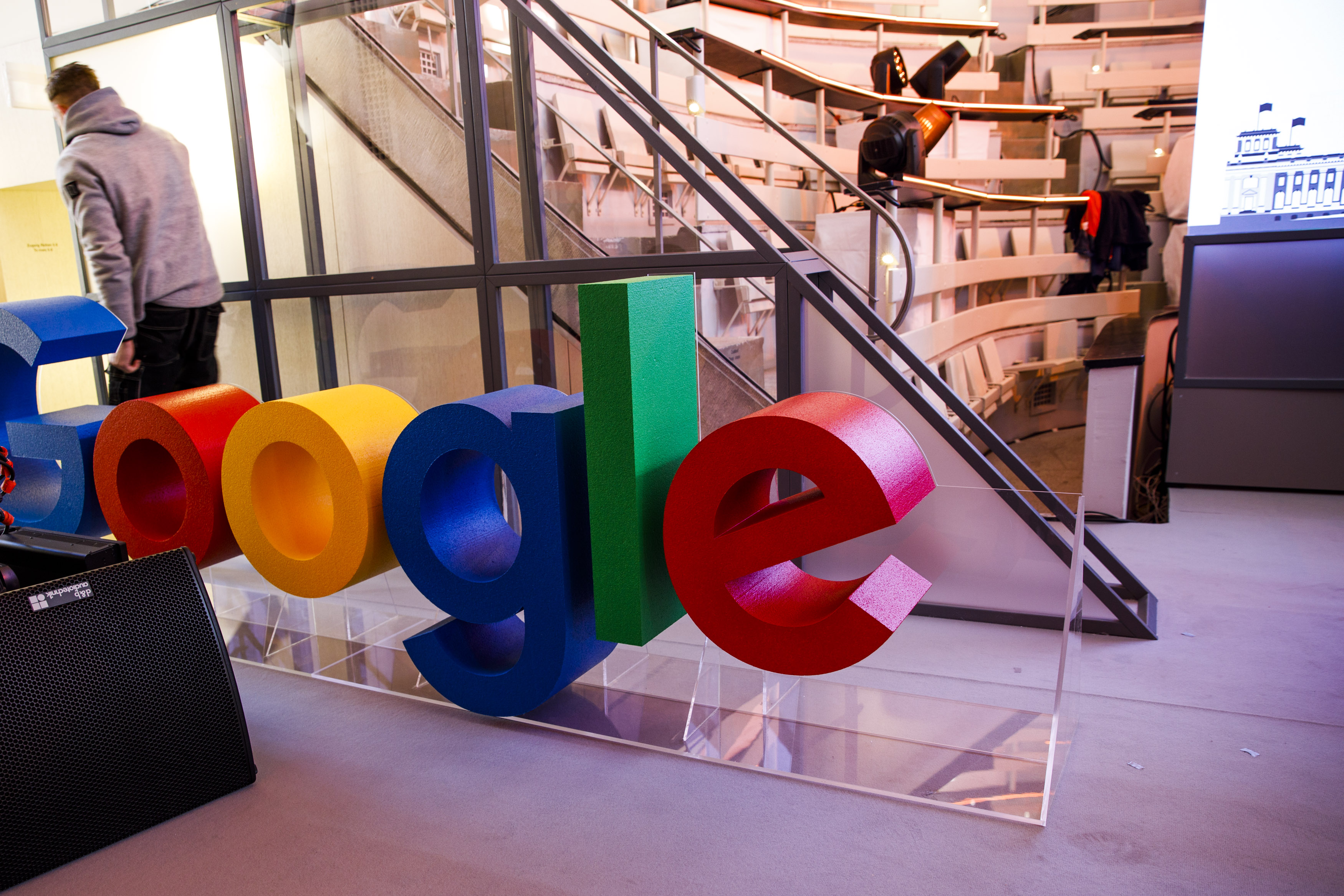 Workers push a Google sign from the stage before the festive opening of the Berlin representation of Google Germany on January 22, 2019 in Berlin, Germany. (Carsten Koall/Getty Images)