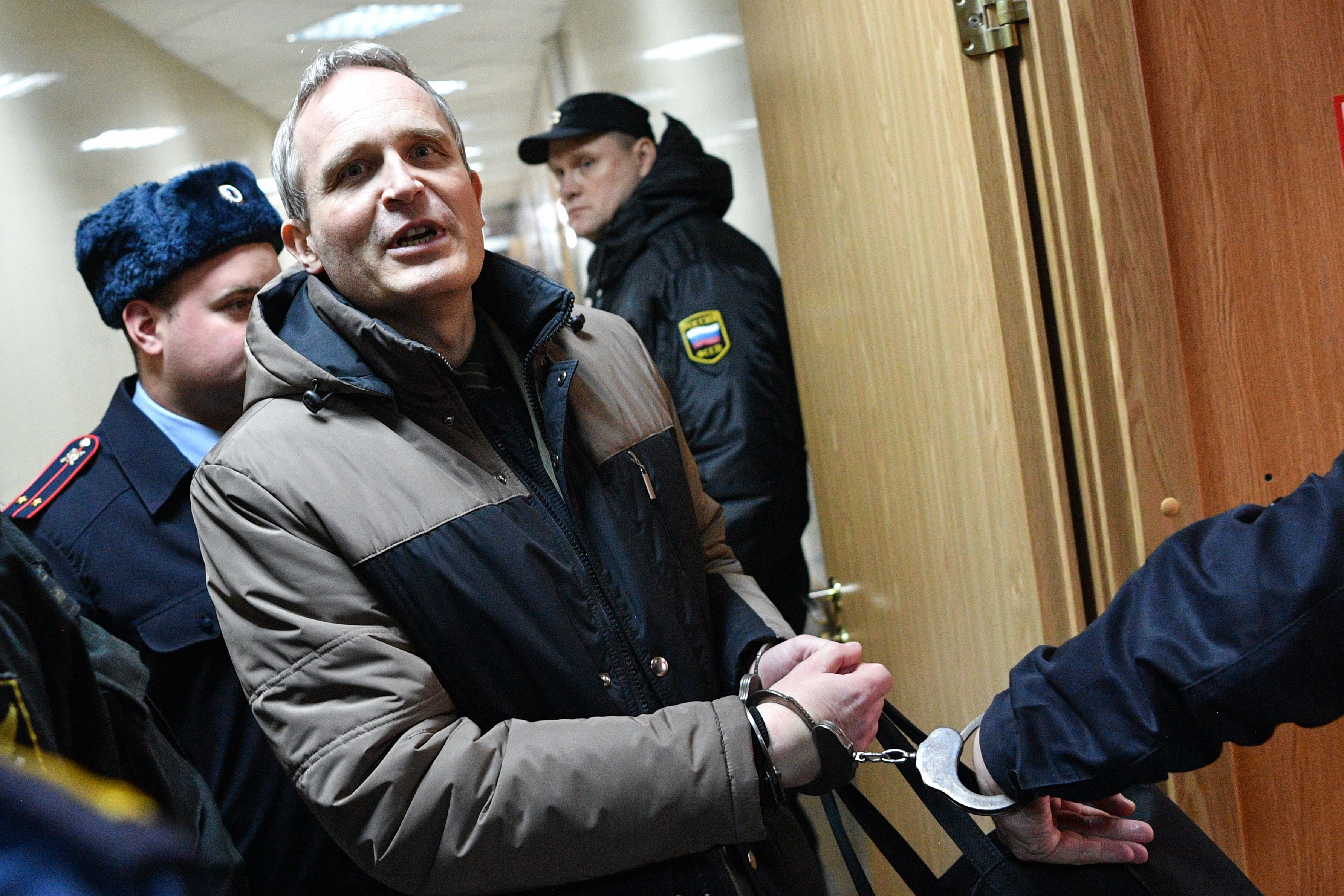 Dennis Christensen, a Danish Jehovah's Witness accused of extremism, is escorted into a courtroom to hear his verdict in the town of Oryol on February 6, 2019. (Photo by Mladen ANTONOV / AFP) (Photo credit should read MLADEN ANTONOV/AFP via Getty Images)