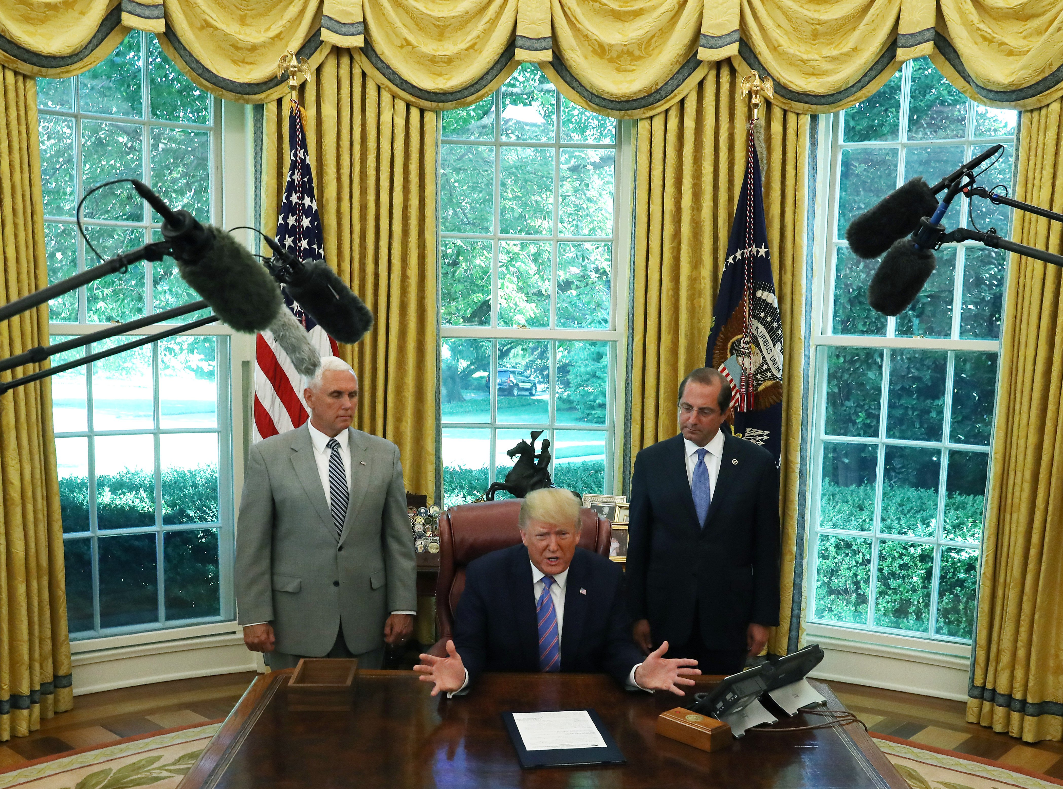 WASHINGTON, DC - JULY 01: US President Donald Trump speaks to the media after signing a bill for border funding legislation while flanked by Vice President Mike Pence (L) and Health and Human Services (HHS) Secretary Alex Azar (R) in the Oval Office at the White House on July 1, 2019 in Washington, DC. (Photo by Mark Wilson/Getty Images)