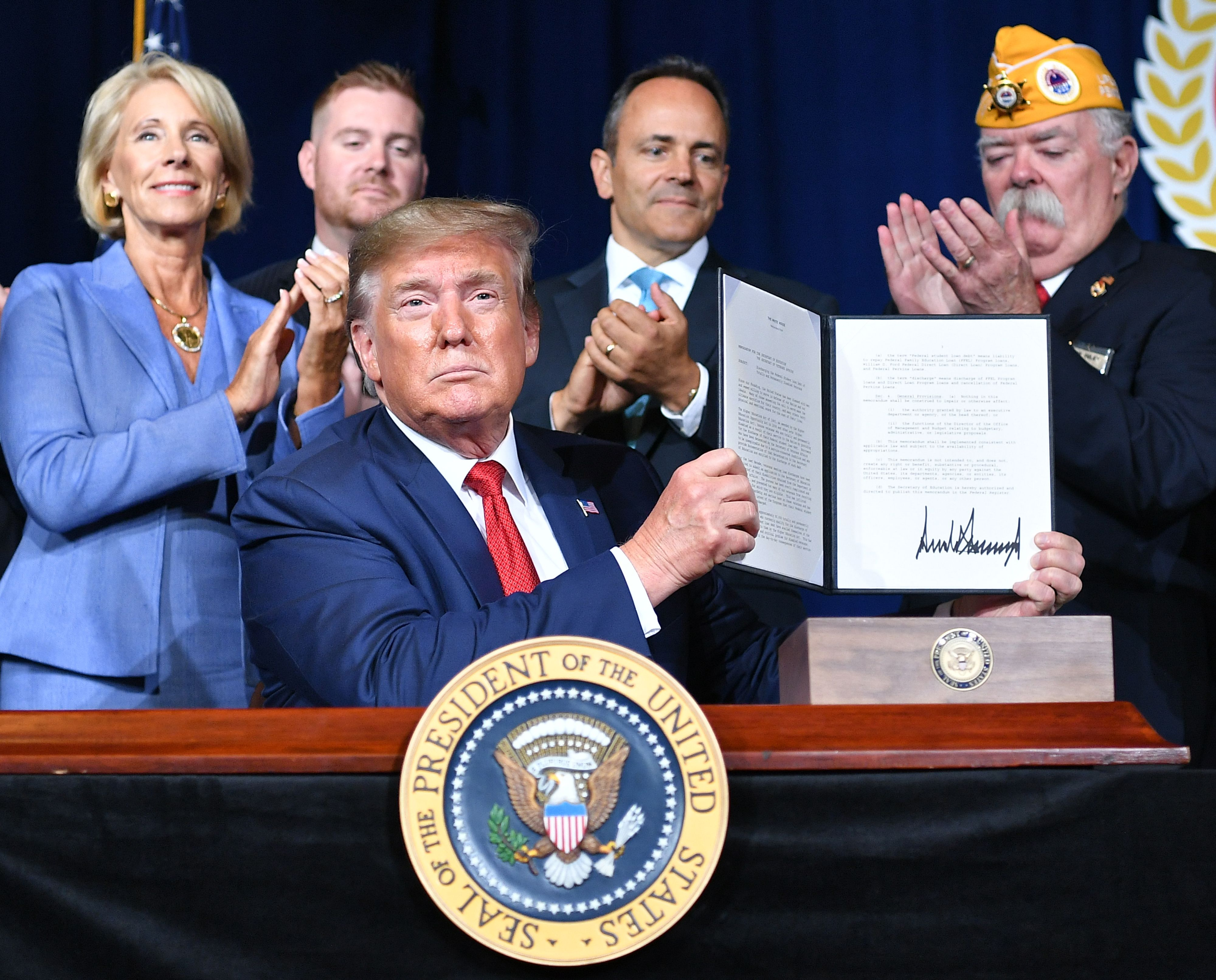 US President Donald Trump sign a Presidential Memorandum on Discharging the Federal Student Loan Debt of Totally and Permanently Disabled Veterans, at the American Veterans (AMVETS) 75th National Convention in Louisville, Kentucky, on August 21, 2019. - With Trump are US Secretary Betsy DeVos (L), Kectucky Governor Matt Bevin (2nd R) and AMVETS National Commander Rege Riley (R). (Photo by Mandel NGAN / AFP) / ALTERNATIVE CROP (Photo credit should read MANDEL NGAN/AFP via Getty Images)