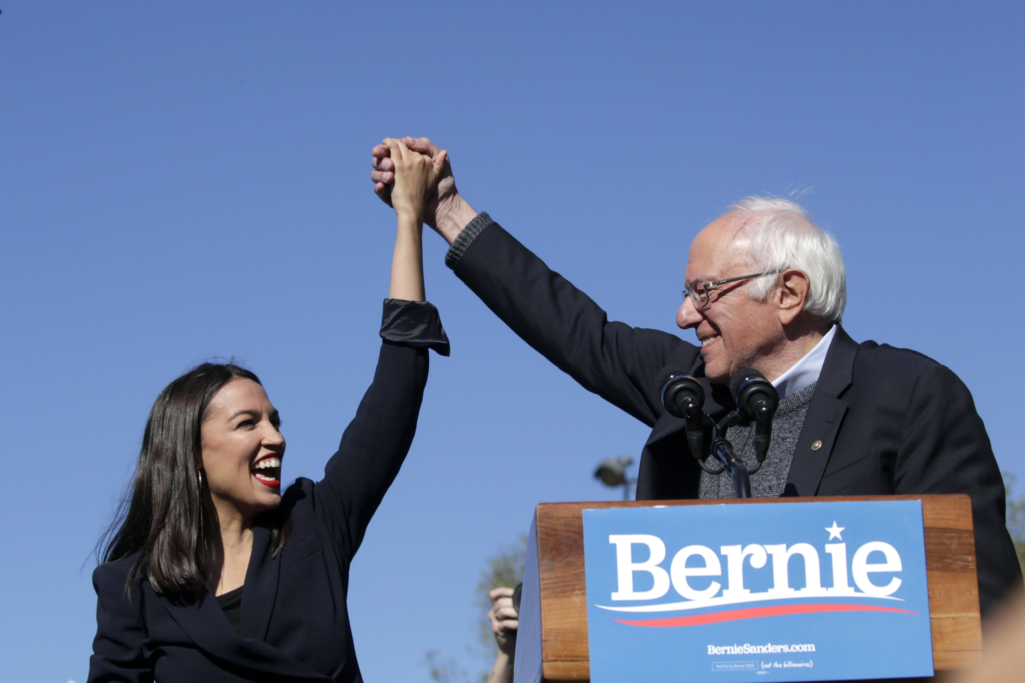 Democratic presidential candidate, Sen. Bernie Sanders (I-VT) holds hands with Rep. Alexandria Ocasio-Cortez (D-NY) during his speech at a campaign rally in Queensbridge Park on October 19, 2019 in the Queens borough of New York City. (Photo by Kena Betancur/Getty Images)