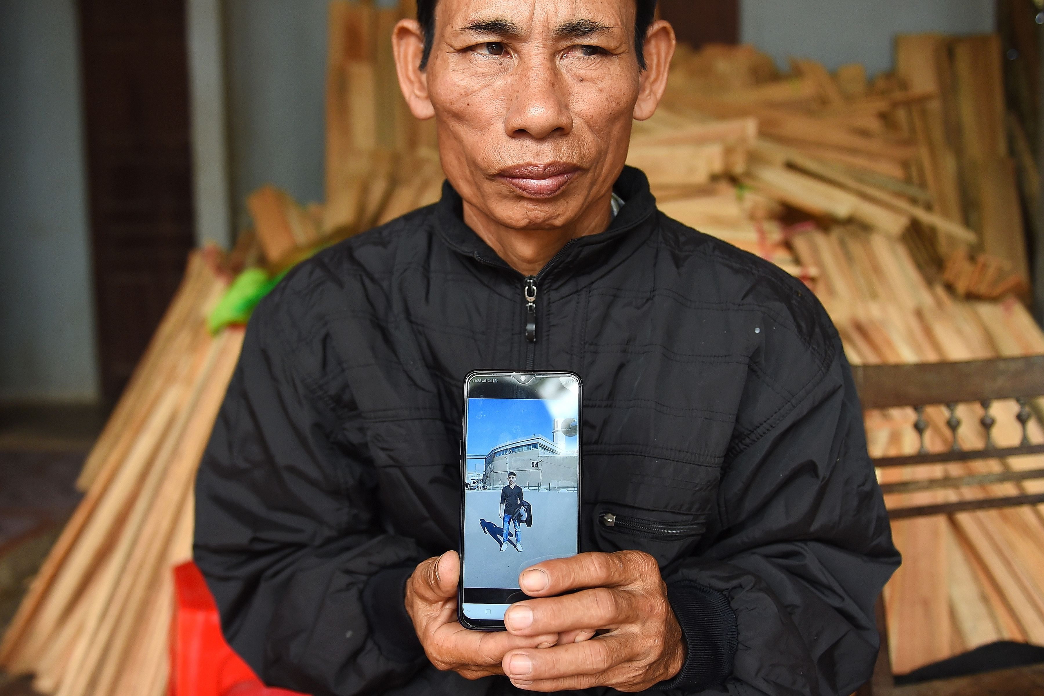 Nguyen Dinh Gia, father of 20-year-old Nguyen Dinh Luong who is feared to be among the 39 people found dead in a truck in Britain, poses with his son's photograph at their house in Can Loc district of Vietnam's Ha Tinh province on October 29, 2019.(NHAC NGUYEN/AFP via Getty Images)